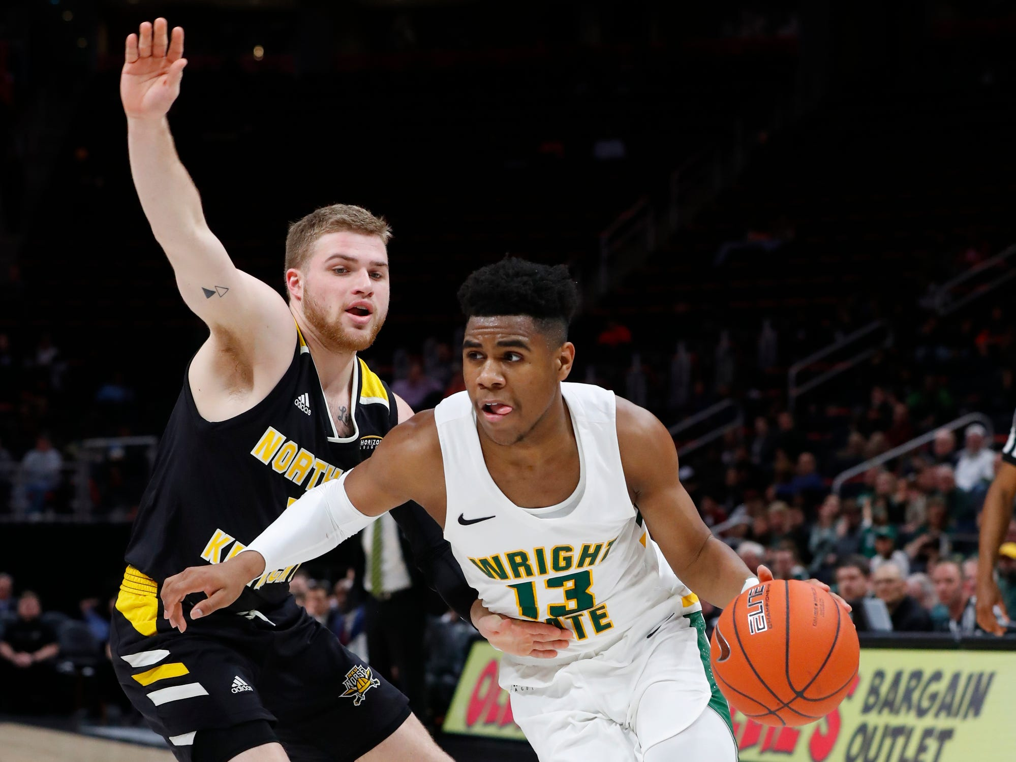 Wright State guard Malachi Smith (13) drives on Northern Kentucky guard Tyler Sharpe (15) in the first half of an NCAA men's basketball game in the Horizon League conference tournament championship in Detroit, Tuesday, March 12, 2019.