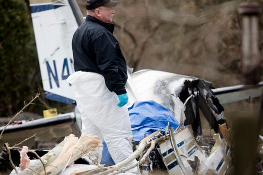 Investigators work the scene of a plane crash on Wednesday, March 13, 2109, on Rollymeade Avenue in Madeira.