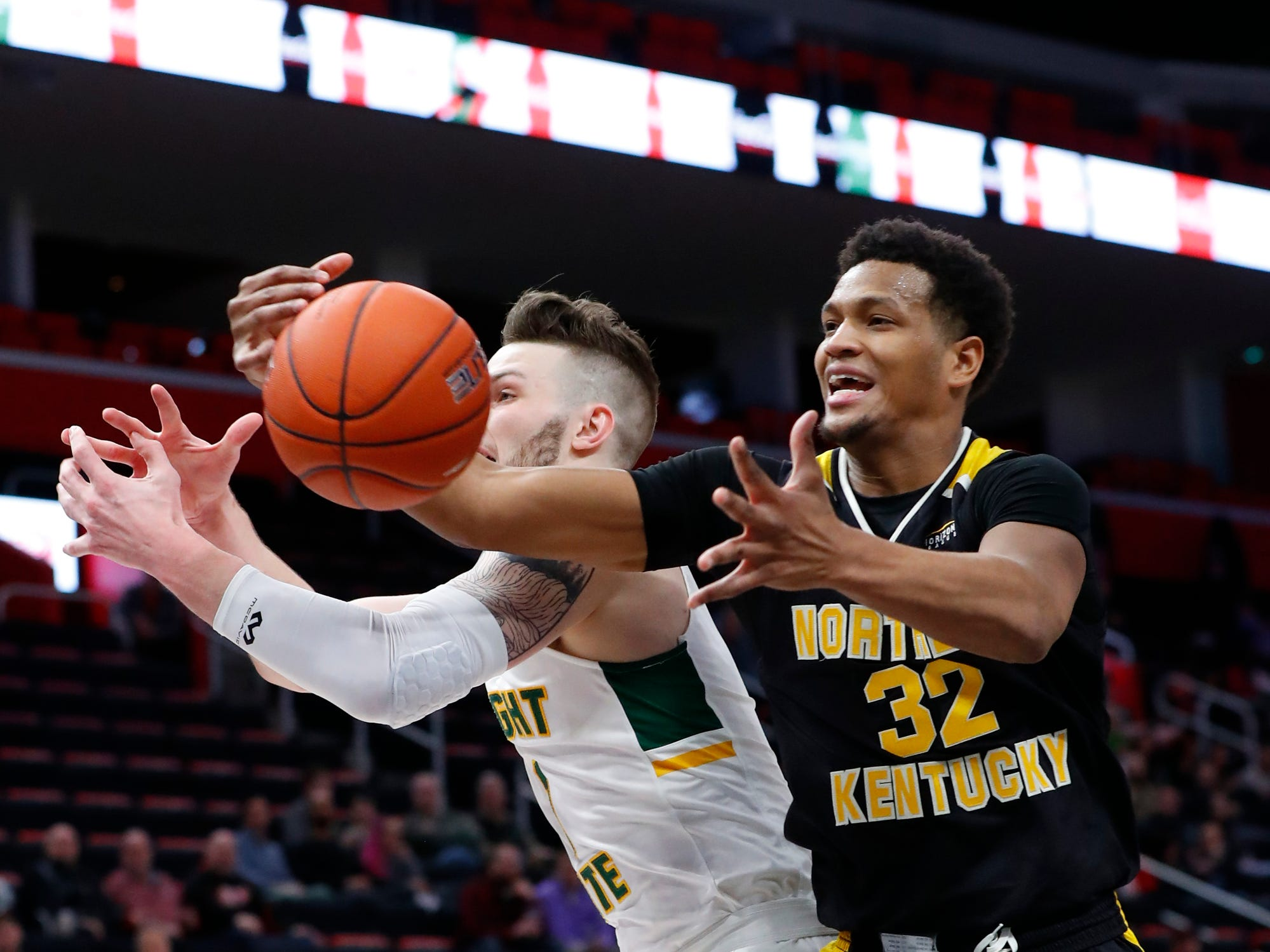 Northern Kentucky forward Dantez Walton (32) pulls down a rebound from Wright State forward Billy Wampler (1) in the first half of an NCAA men's basketball game in the Horizon League conference tournament championship in Detroit, Tuesday, March 12, 2019.