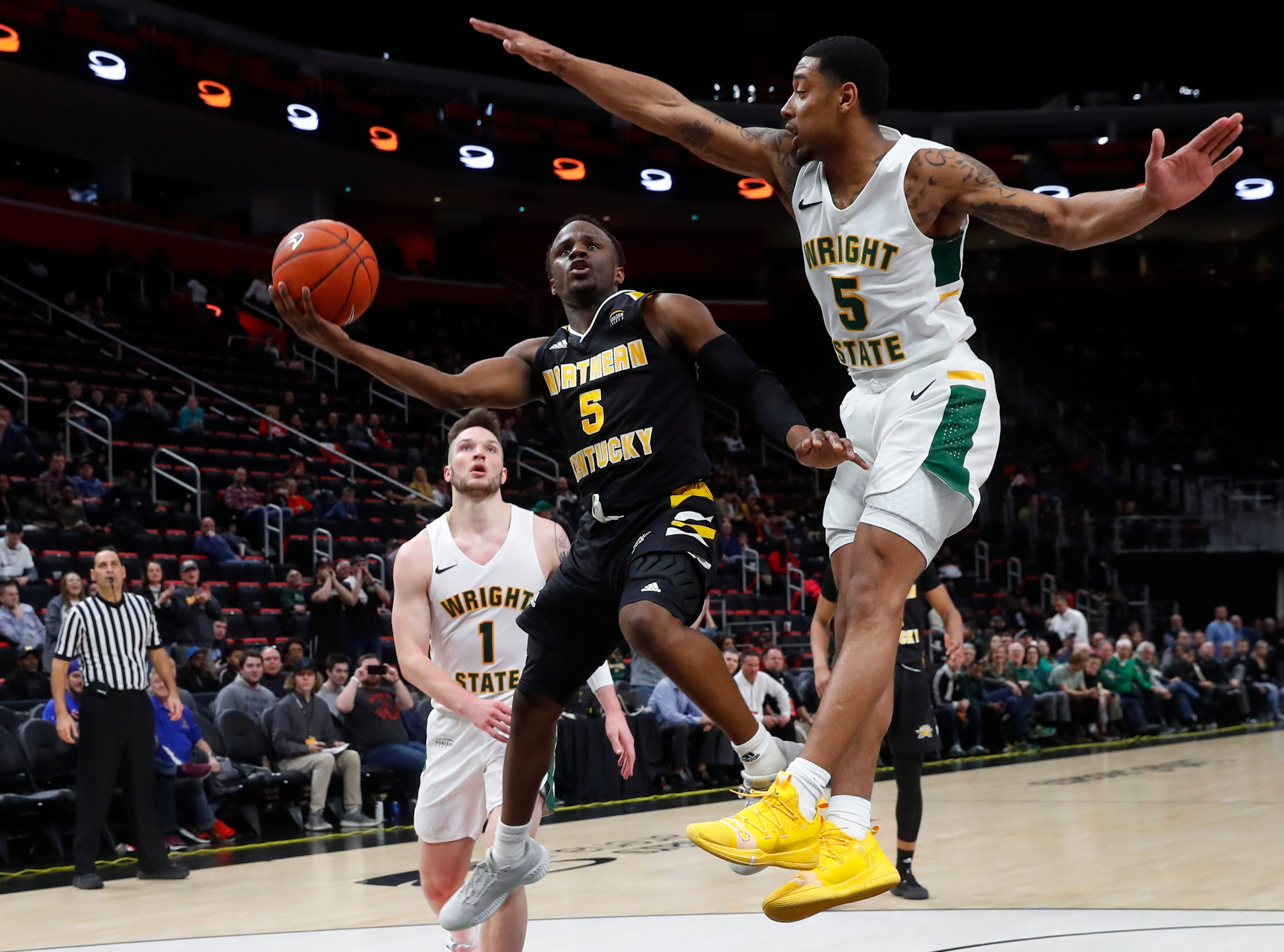 Northern Kentucky guard Zaynah Robinson (5) drives on Wright State guard Skyelar Potter (5) during the second half of an NCAA college basketball game for the Horizon League men's tournament championship in Detroit, Tuesday, March 12, 2019.