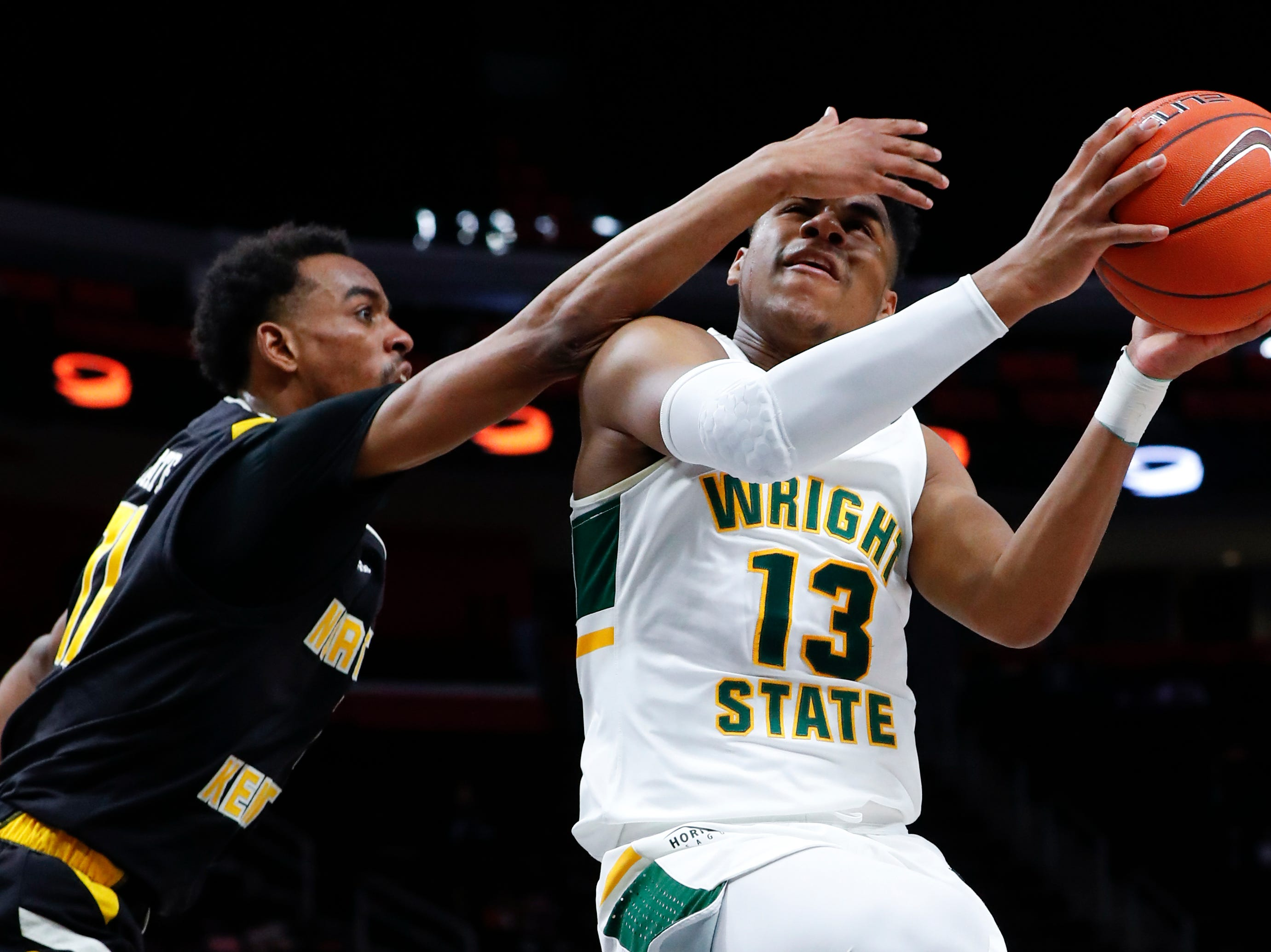 Wright State guard Malachi Smith (13) drives on Northern Kentucky guard Jalen Tate (11) during the first half of an NCAA college basketball game for the Horizon League men's tournament championship in Detroit, Tuesday, March 12, 2019.