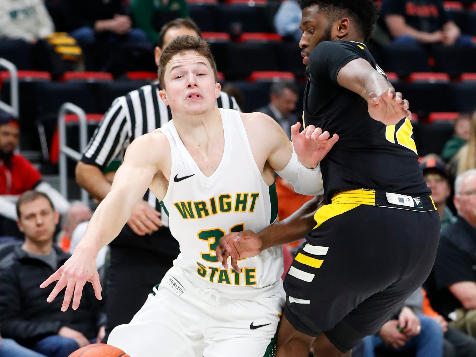 Wright State guard Cole Gentry (31) drives on Northern Kentucky guard Trevon Faulkner (12) in the first half of an NCAA men's basketball game in the Horizon League conference tournament championship in Detroit, Tuesday, March 12, 2019.