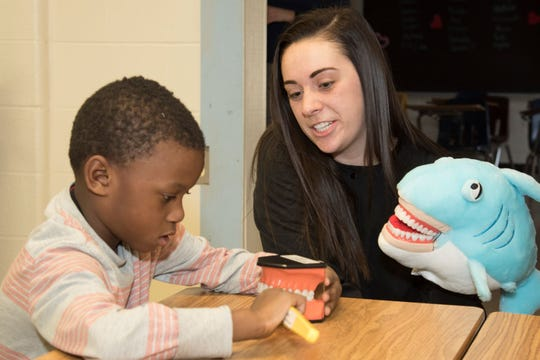 UC Blue Ash dental hygiene student Jenny Schramm teaches proper brushing techniques to a student at Riverview East Academy.
