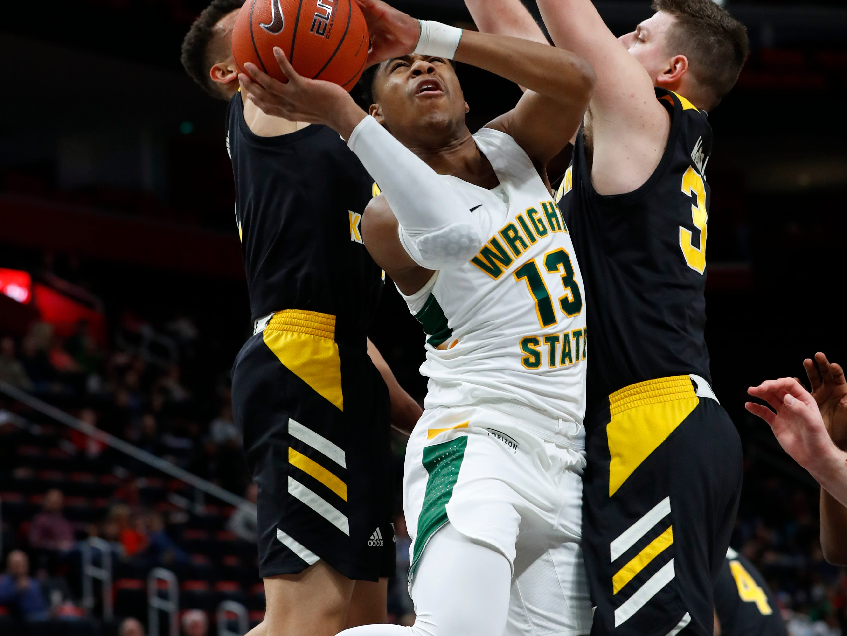 Wright State guard Malachi Smith (13) drives between Northern Kentucky guard Paul Djoko and forward Drew McDonald (34) during the first half of an NCAA college basketball game for the Horizon League men's tournament championship in Detroit, Tuesday, March 12, 2019.