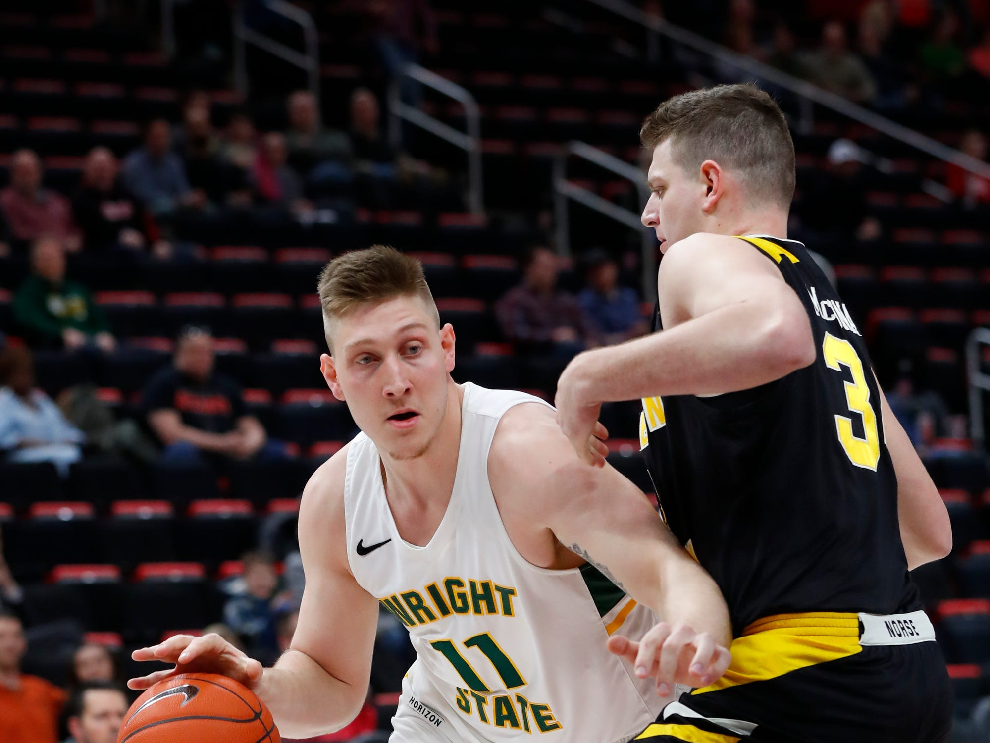 Wright State center Loudon Love (11) drives on Northern Kentucky forward Drew McDonald (34) in the first half of an NCAA men's basketball game in the Horizon League conference tournament championship in Detroit, Tuesday, March 12, 2019.