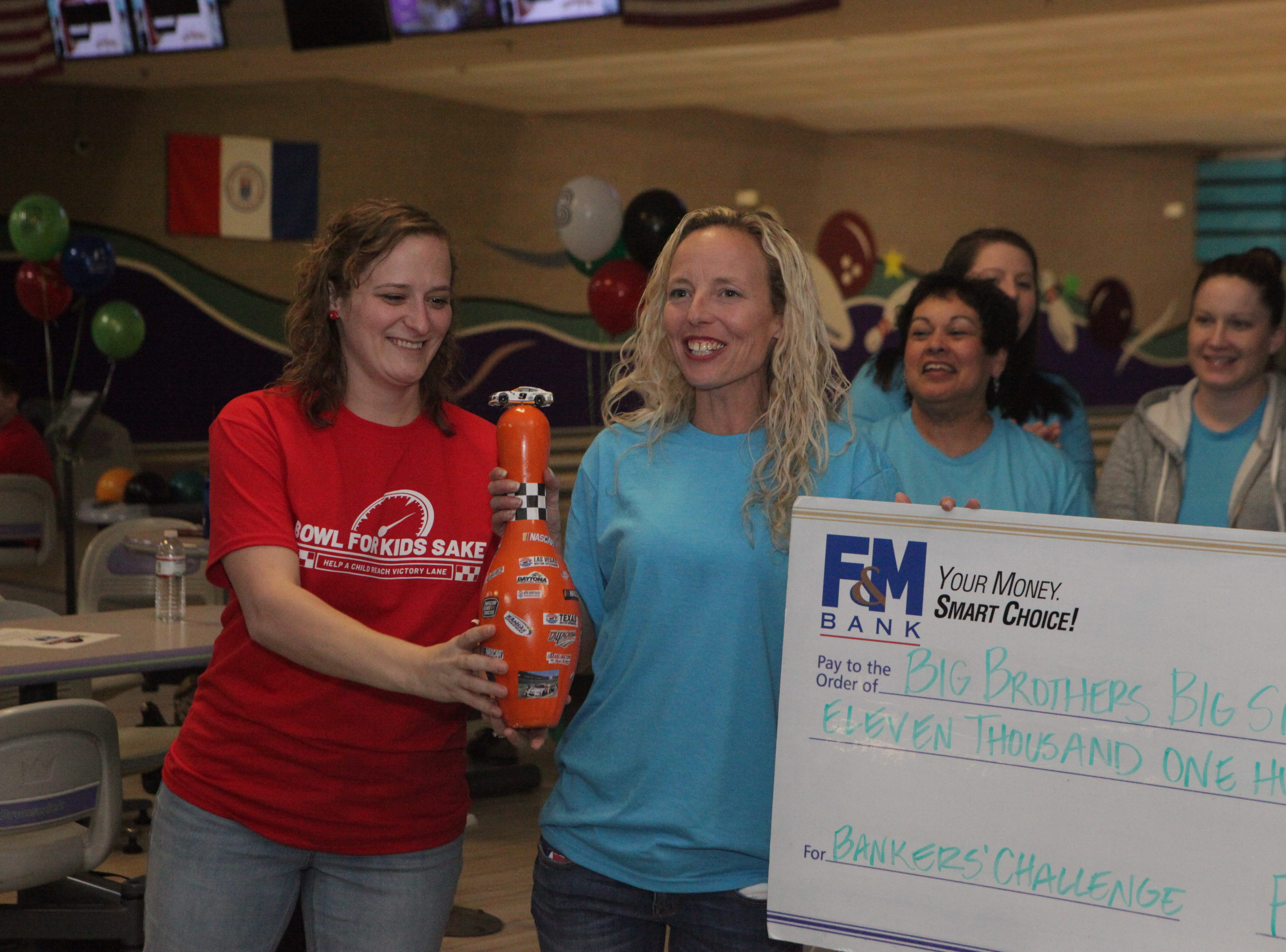 Jess Little of Big Brothers Big Sisters presents the trophy for Top Fundraising Team to Stacey Streetman and F&M Bank at the 2019 Bankers Challenge at the Pinnacle Family Entertainment Center on Tuesday, March 12, 2019.