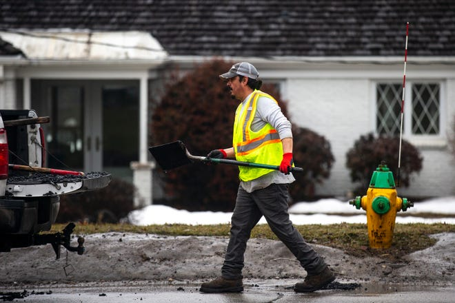 A city of Des Moines worker patches pot holes on Fleur Drive in March.