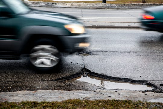 Drivers dodge pot holes along Fleur Drive on Wednesday, March 13, 2019, in Des Moines.