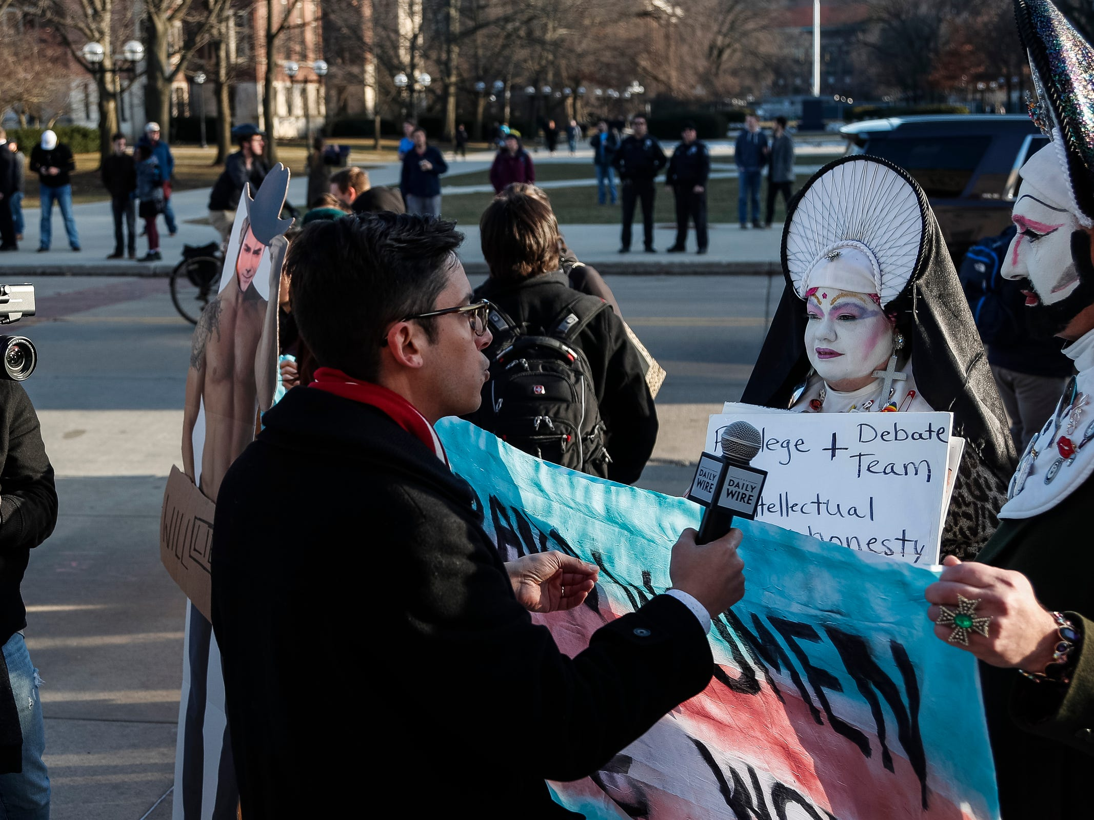 Michael Knowles, a show host from the Daily Wire, center, interviews Motor City Sisters of Perpetual Indulgence's Sister Ima W Anchor, far right, who shows her support transgender women outside of the Rackham Auditorium on U-M central campus in Ann Arbor, Tuesday, March 12. , Tuesday, March 12, 2019.