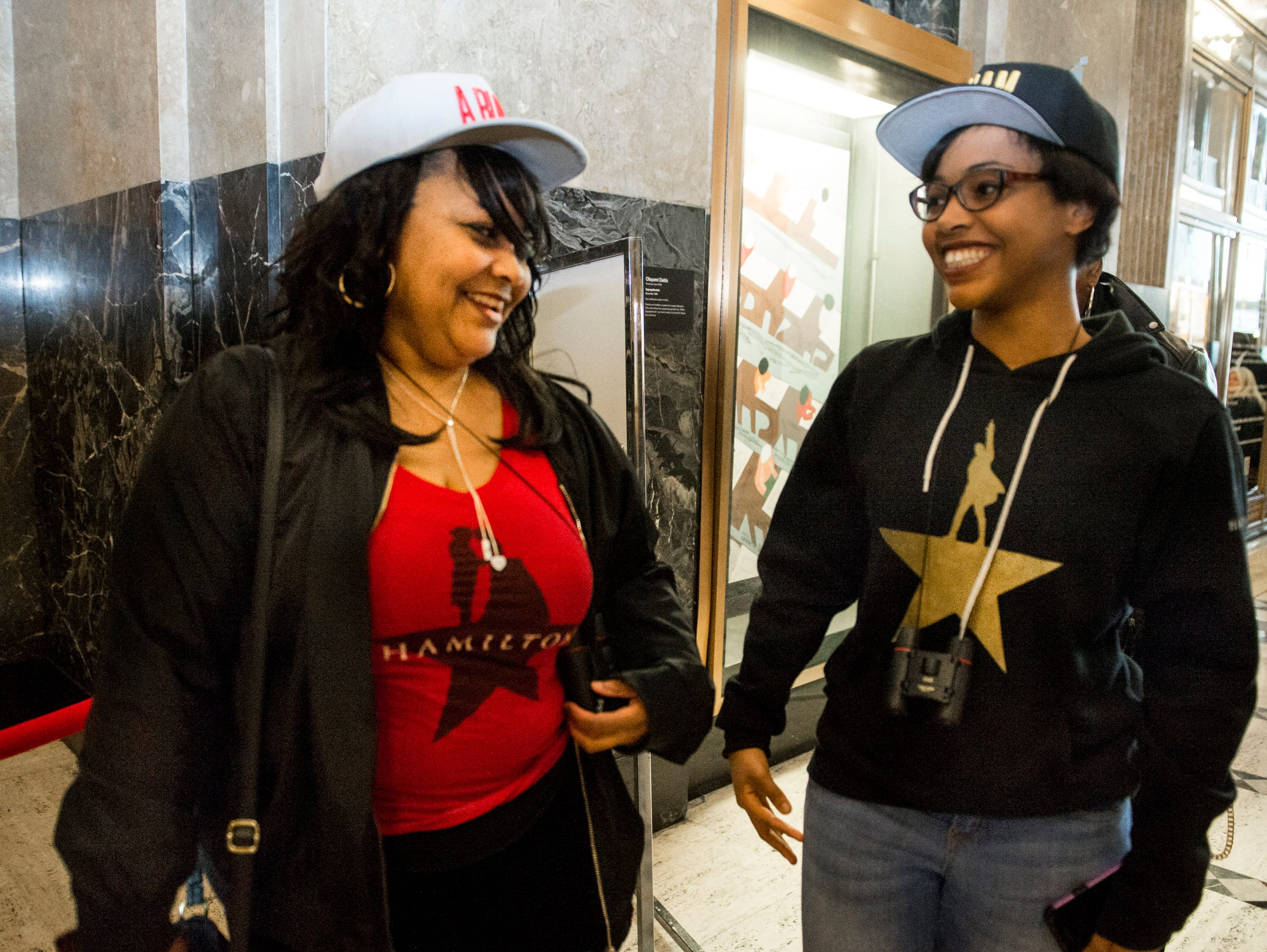 Wearing dueling Hamilton and Burr T-shirts, Briana Rowe, left, and daughter Camisha Hughbanks prepare to enter the Fisher.