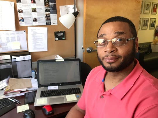 Bryan Jones, 52, of Detroit sits at his desk in Detroit and says he's lucky his boss looked past his prison background and hired him for his positive attitude and office skills.