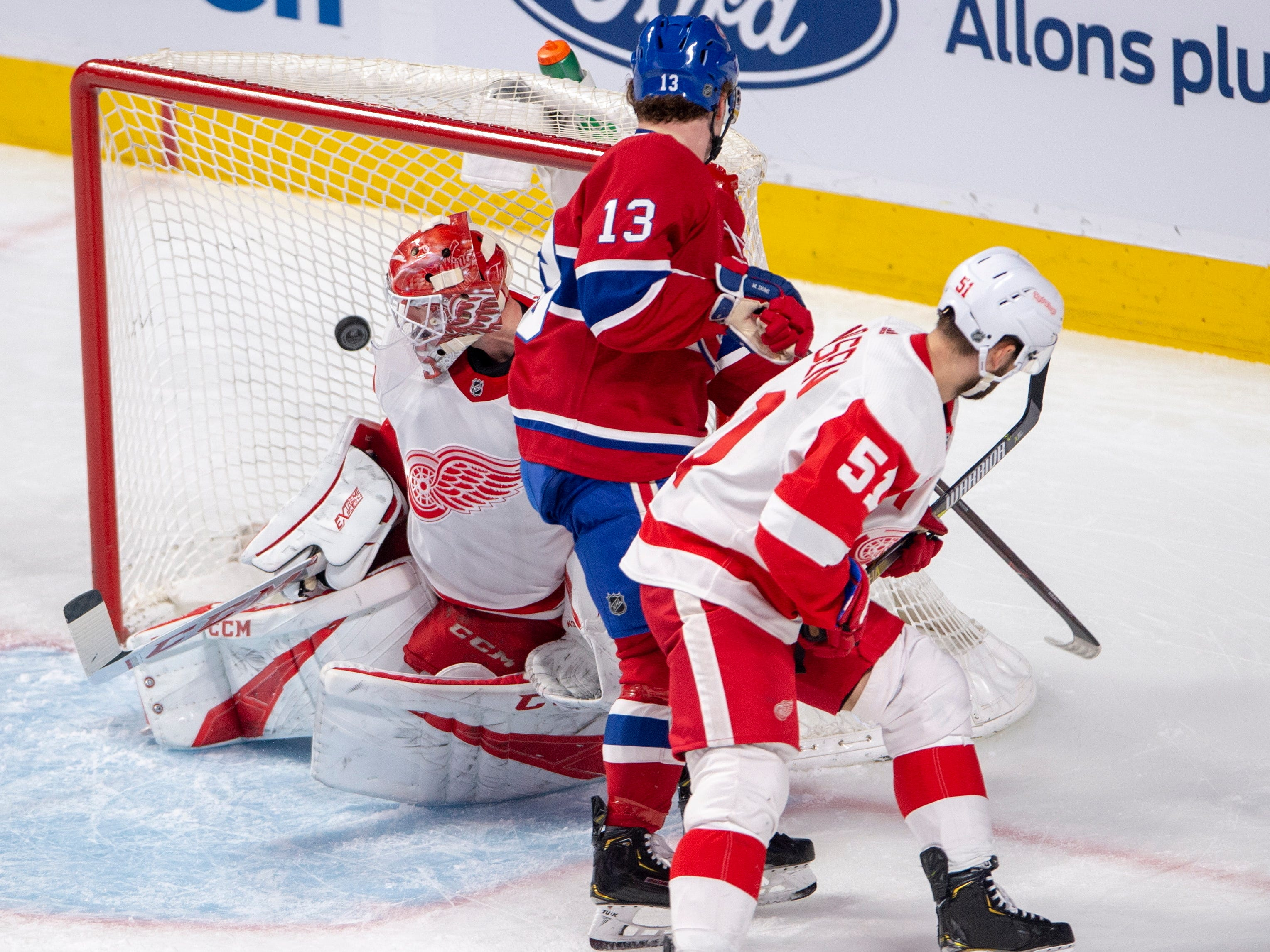 Montreal Canadiens center Max Domi (13) scores against Detroit Red Wings goaltender Jonathan Bernier, as Red Wings center Frans Nielsen defends during the second period Tuesday, March 12, 2019, in Montreal.