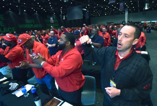 From right, Region 5 Local 31 UAW delegates Dan Kandlbinder and Anthony Walker, both of Kansas City, Missouri, cheer while UAW President Gary Jones speaks.