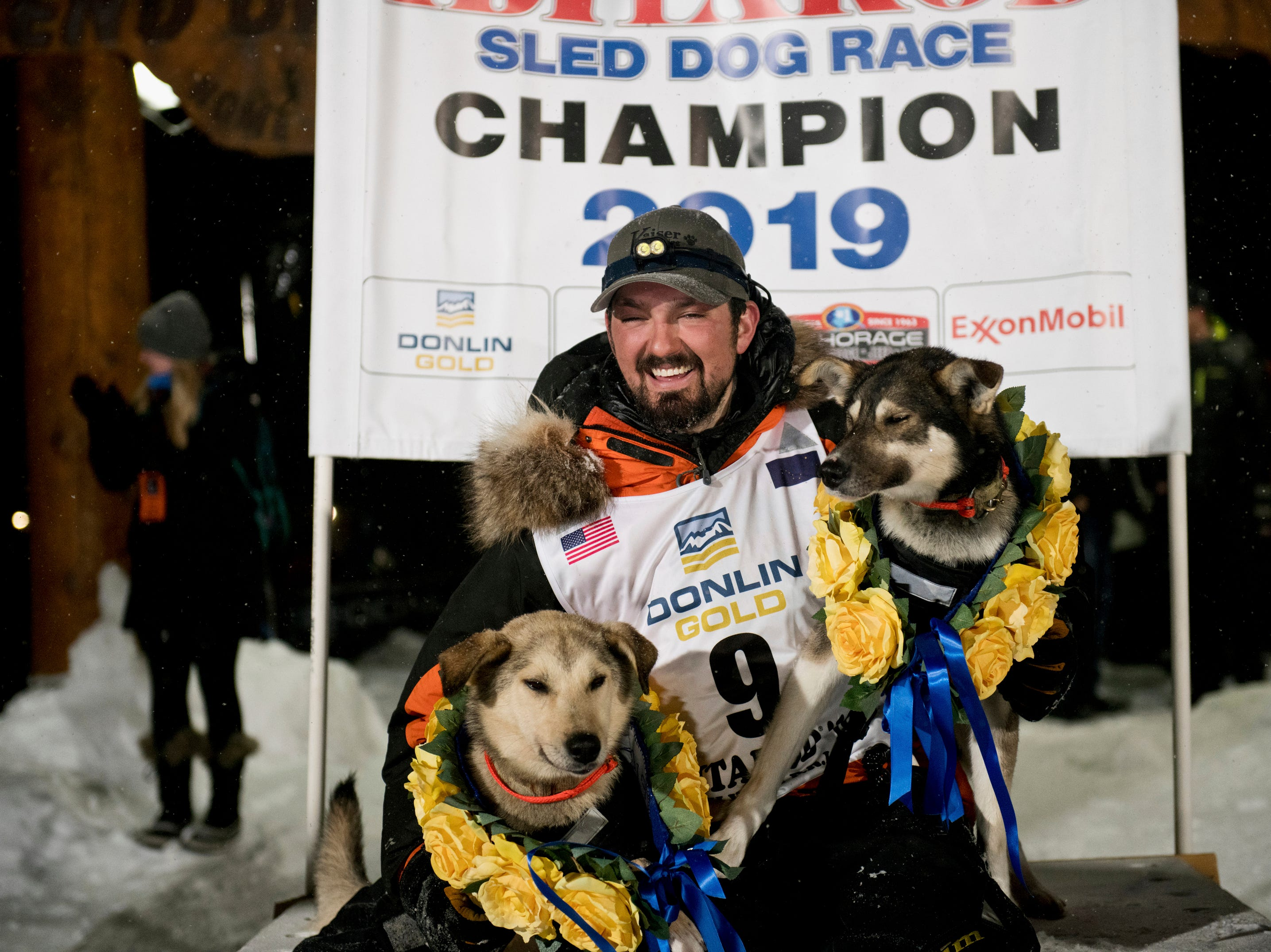 Alaskan Peter Kaiser poses with lead dogs, Morrow, left, and Lucy on Wednesday, March 13, 2019, in Nome, Alaska, after winning his first Iditarod Trail Sled Dog Race in 10 attempts.
