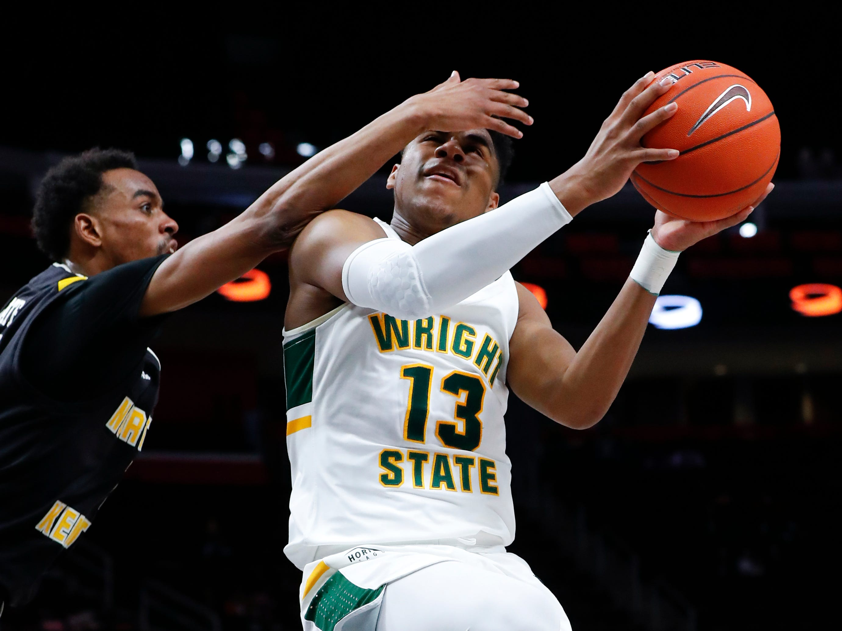 Wright State guard Malachi Smith (13) drives on Northern Kentucky guard Jalen Tate (11) during the first half.