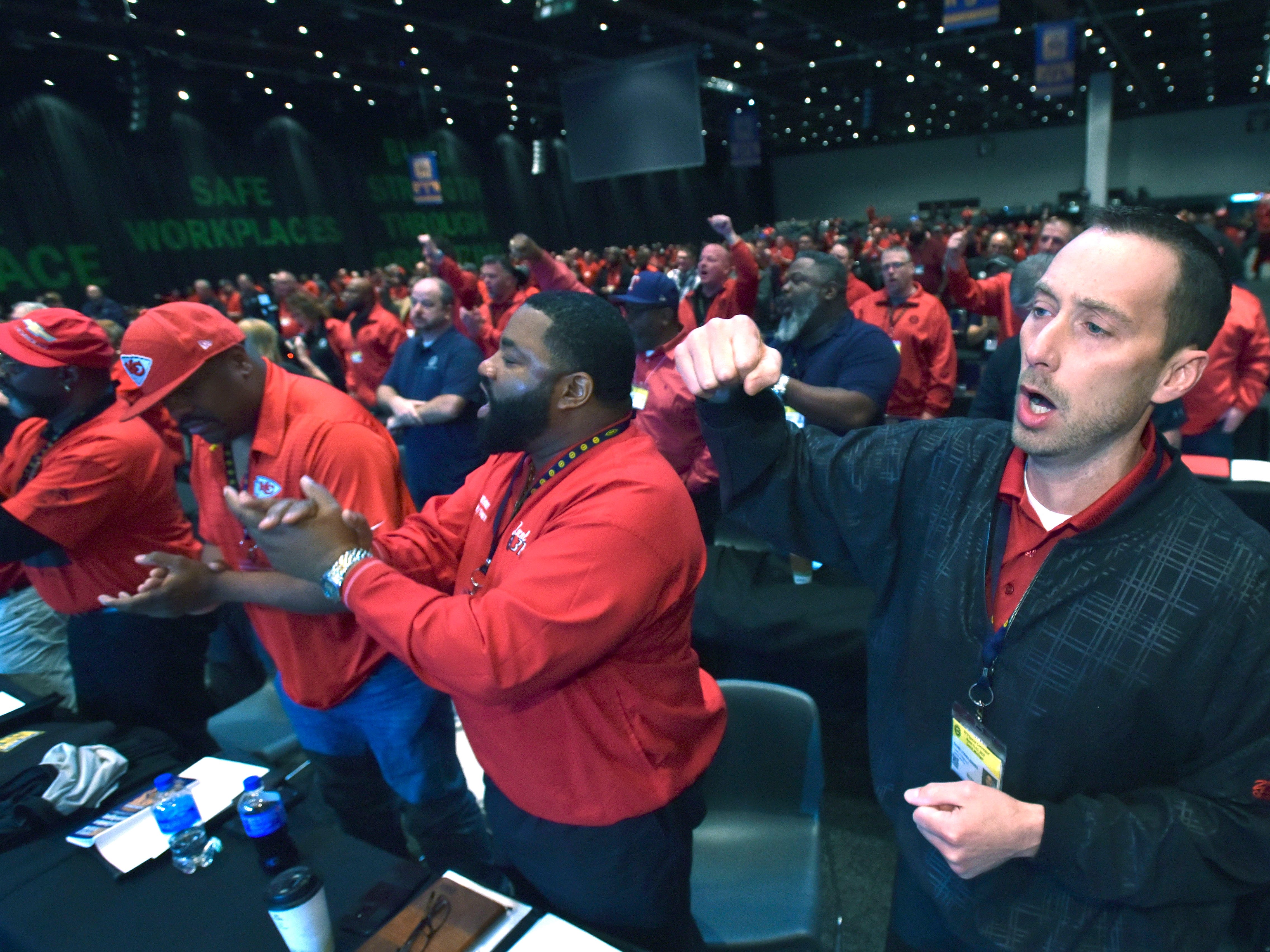 From right, Region 5 Local 31 UAW delegates Dan Kandlbinder and Anthony Walker, both of Kansas City, Missouri, cheer during UAW Gary Jones' address.