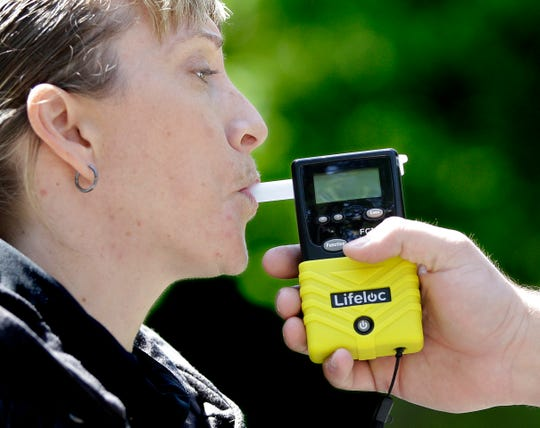 California Highway Patrol Sgt. Jaimi Kenyon blows into a breathalyzer held by Sacramento Police Corporal Luke Moseley during a demonstration of devices used to test drivers suspected of impaired driving Wednesday, May 10, 2017, in Sacramento, Calif. Breathalyzers are commonly used to detect alcohol but a new device tested by three of California's largest counties, can detect the presence of drugs in saliva within five minutes. Some officers and lawmakers want the devices used statewide after voters passed Proposition 64 in November, legalizing the recreation douse of marijuana.