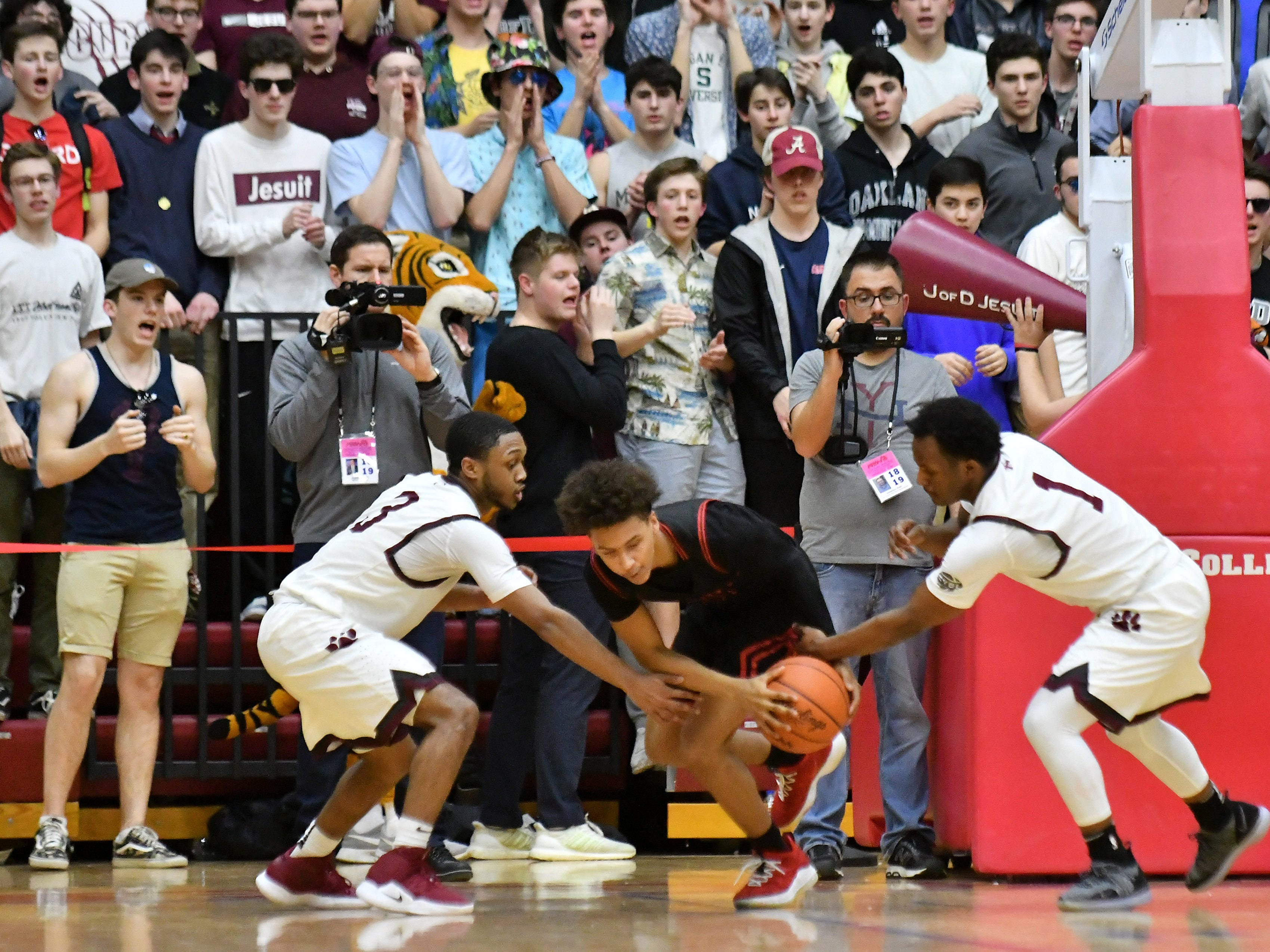 U-D Jesuit's Jordan Montgomery, left, and Julian Dozier, right, try to get the ball from Roseville's Isiah Collier-Foutz in the first half.