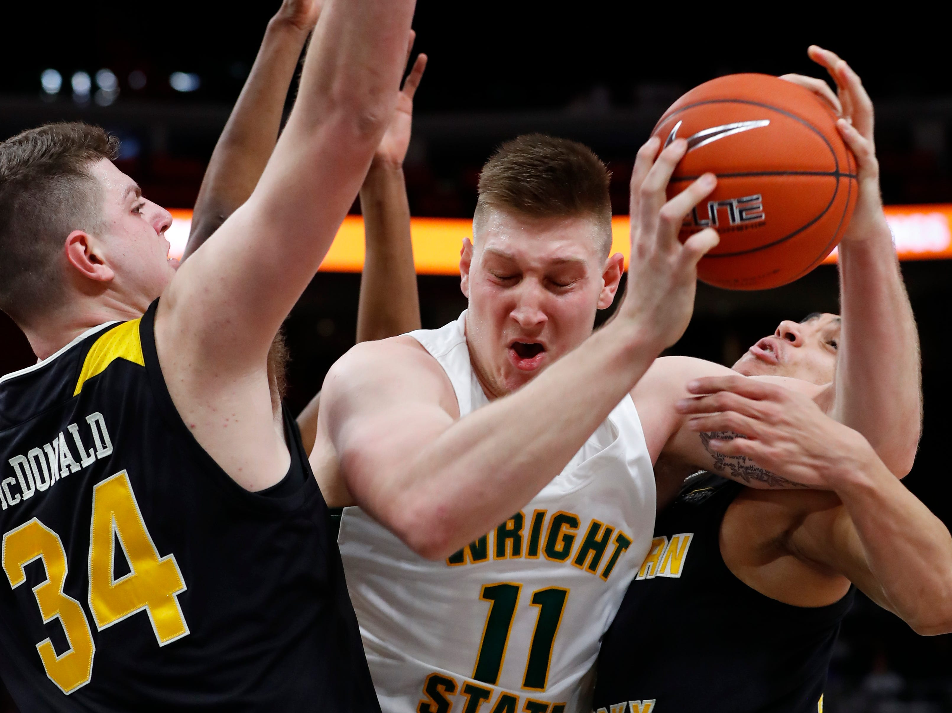 Wright State center Loudon Love (11) tries to drive between Northern Kentucky forward Drew McDonald (34) and Northern Kentucky guard Paul Djoko (2) in the first half of the Horizon League conference tournament championship in Detroit, Tuesday, March 12, 2019.