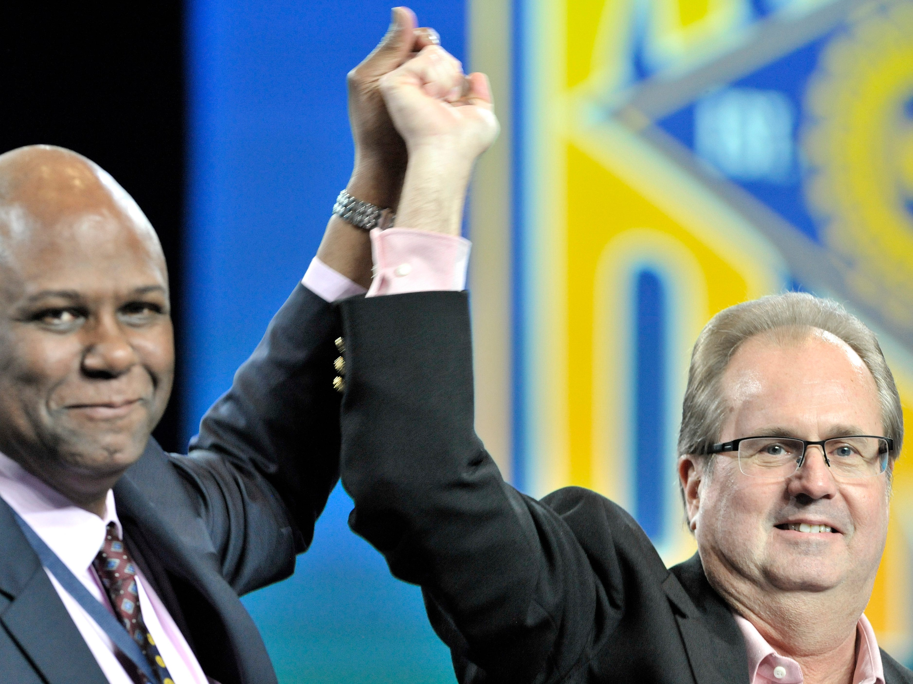 UAW Secretary Treasurer Raymond Curry, left, and President Gary Jones raise their hands after greeting members of the UAW Ford National Negotiating Team.