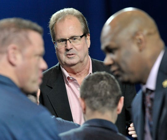 UAW President Gary Jones, center, and secretary-treasurer Raymond Curry, right, greet members of the Ford National Negotiating Team after they are recognized during the special convention.