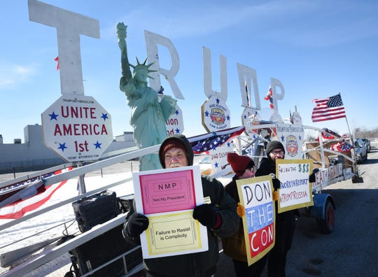 Protestors against President Donald Trump, Larry Biggs, Amethyst Thout and Stavros Glitsos, stand in front of a pro-President Donald Trump trailer during a protest at Willow Run Airport.