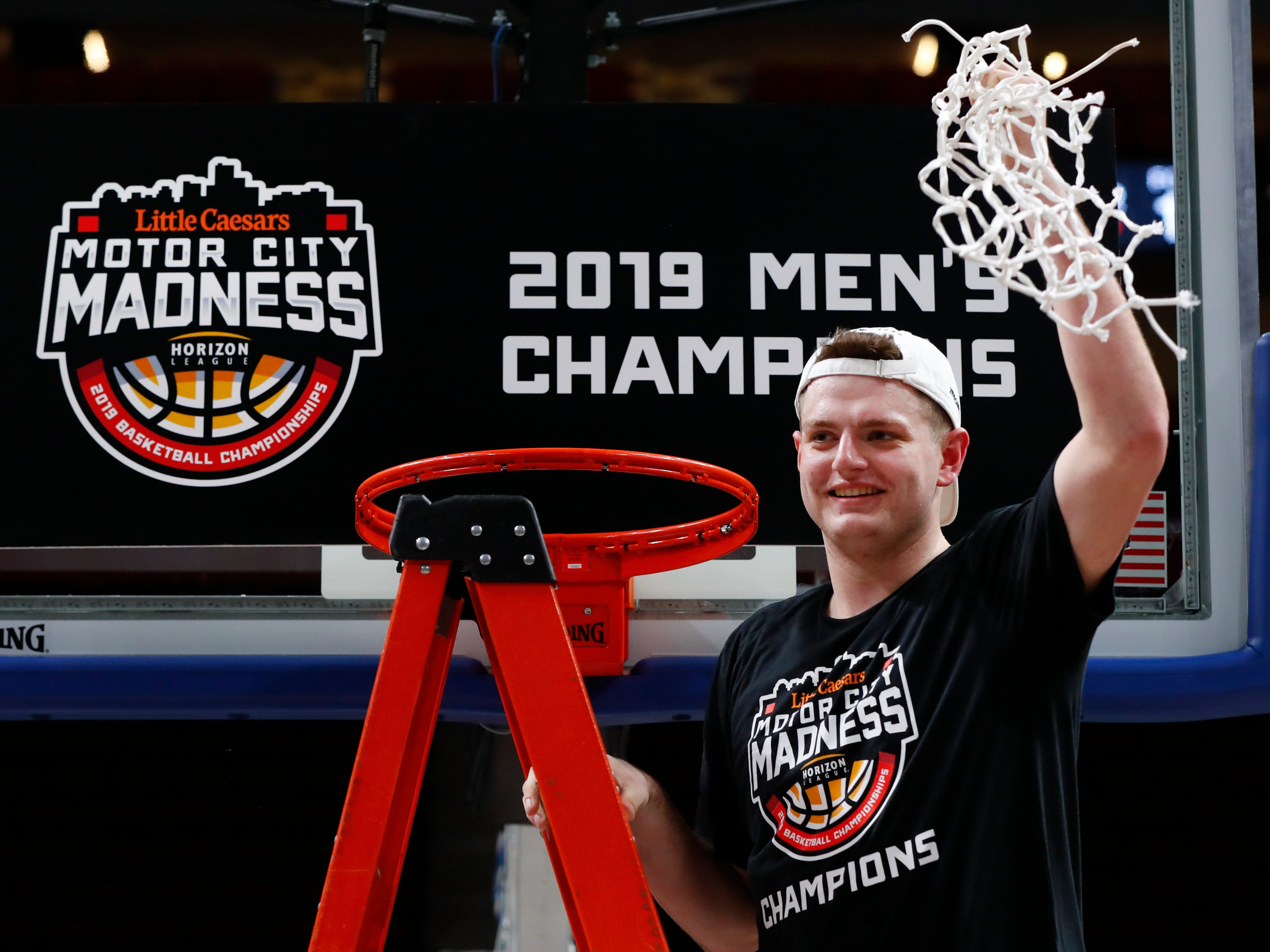 Northern Kentucky's Drew McDonald holds up the net after the team's 77-66 win against Wright State in an NCAA college basketball game for the Horizon League men's tournament championship in Detroit.