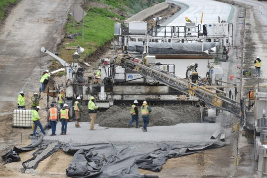Road construction crews use heavy equipment to pour and level concrete along I696 at Thomas Street in Warren on October 12, 2018.