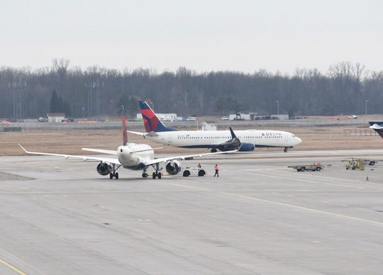 Passengers on a Delta flight from Indianapolis to Detroit Metro Airport restrained a woman who tried to open the plan door shortly after take-off, officials say.