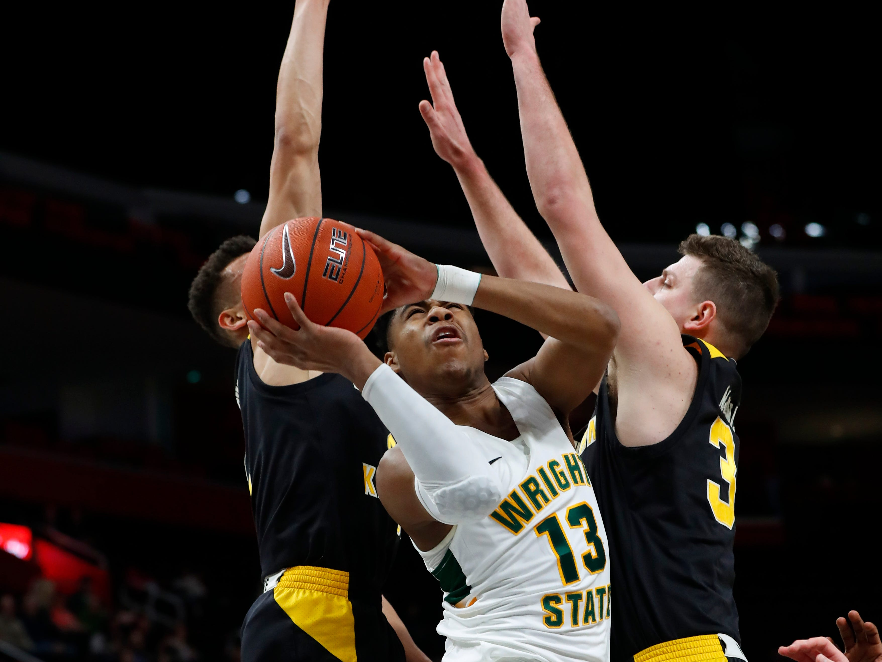 Wright State guard Malachi Smith (13) drives between Northern Kentucky guard Paul Djoko and forward Drew McDonald (34) during the first half.