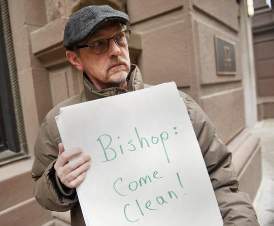David Clohessy, 62, of St. Louis, Mo, a victim of sexual abuse from a member of the Catholic Church, holds a sign during a protest in Detroit on Wednesday.
