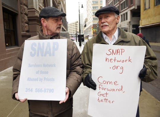 David Clohessy, 62, of St. Louis, Mo, (left) and Allan Kosack, 88, of Royal Oak, walk on State St. to protest abuse by the Catholic Church on Wednesday, March 13.