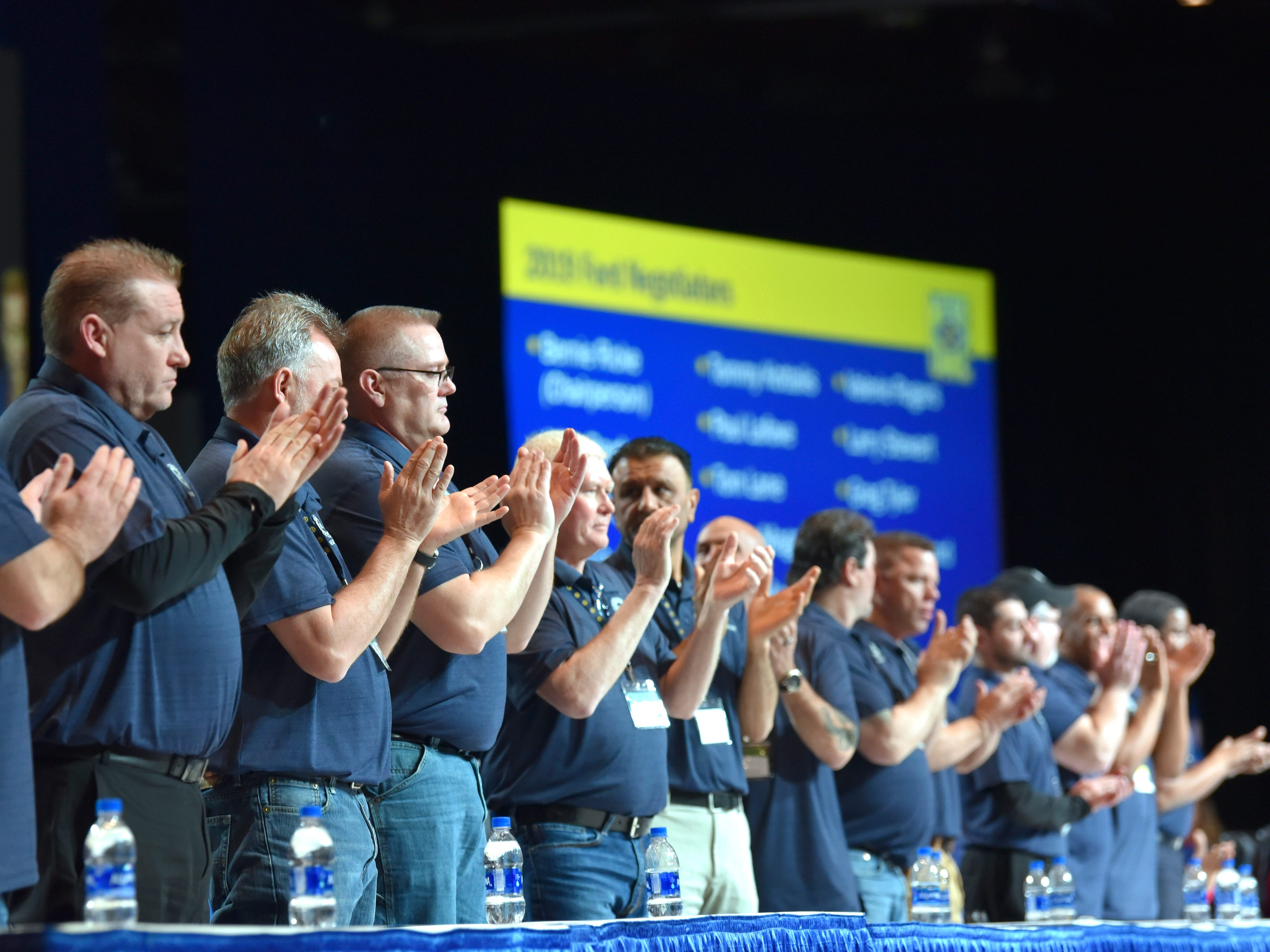Members of the UAW Ford National Negotiating Team stand up as they are recognized during the special convention.