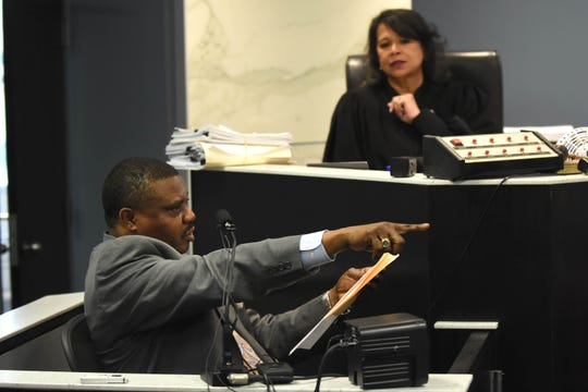 Chidi Nyeche points towards Robert Carmack as Judge Cylenthia Miller looks on as he testifies on the witness stand during a hearing on Carmack's controversial sale of $1 million worth of land in the city of Detroit.