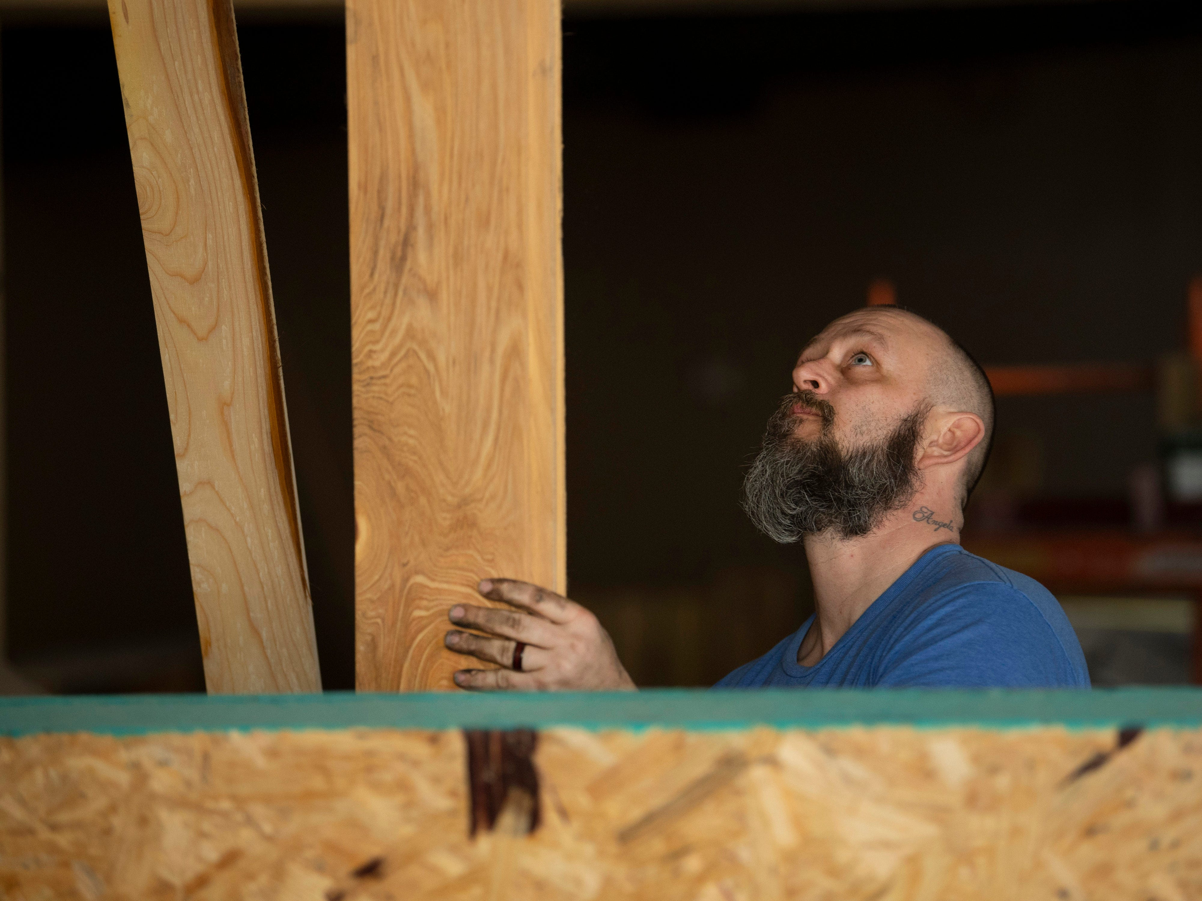 Chris Rutter, a woodworker with The Johnson Wood Shed, stacks cypress planks as work on Bud's Rockin' Country Bar & Grill at 2116 W. Franklin Street in Evansville continues Wednesday afternoon.