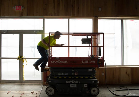 Nate Perkins positions himself on a lift to attach wooden trim to the wall of Bud's Rockin' Country Bar & Grill at 2116 W. Franklin Street in Evansville Wednesday afternoon. Perkins works with The Johnson Wood Shop who is using cypress throughout the bar's interior.