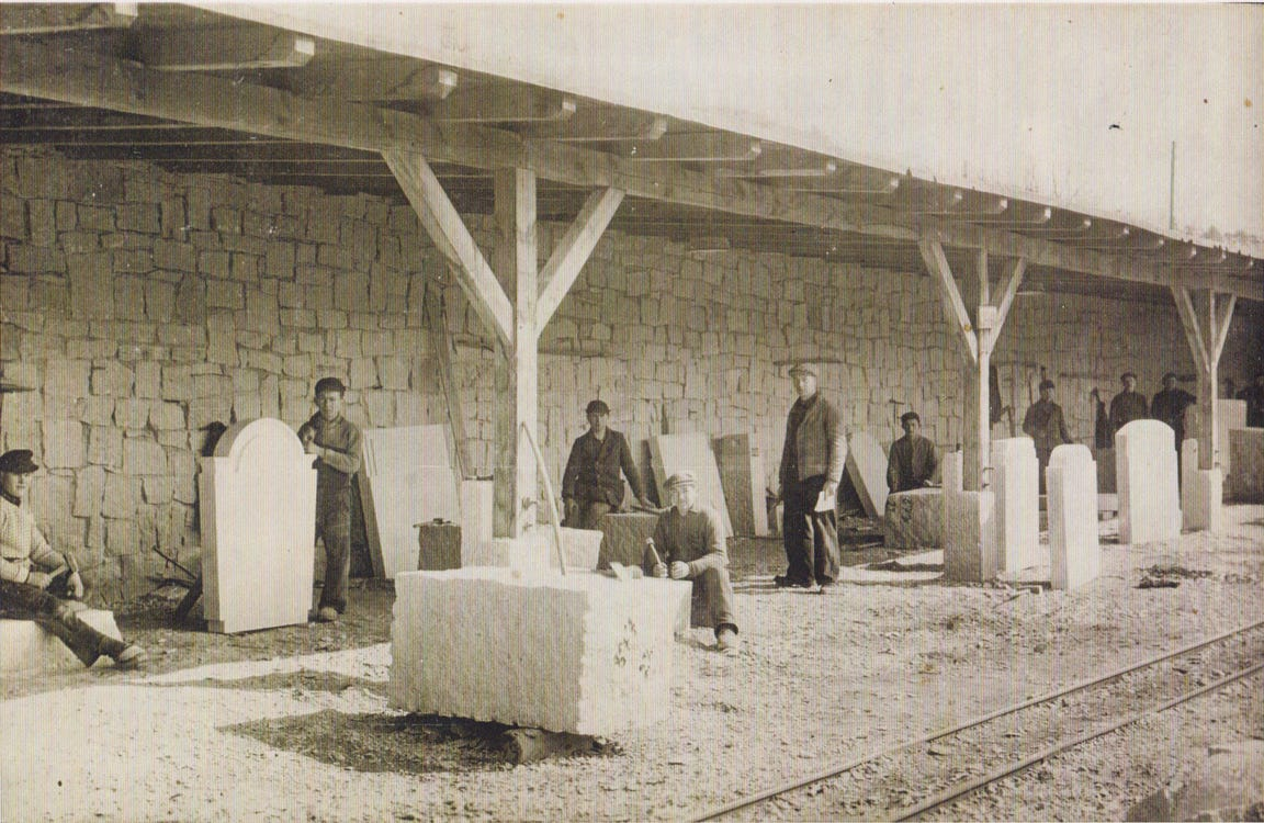 Kurt Pechmann, center, sits in front of a large block of granite in Germany in April 1941. At the time, he was already drafted into the German  Army, but the government said he needed to finish this work first. The stone become a windowsill in Berlin's Bundestag building, said his son, Gerhard Pechmann.