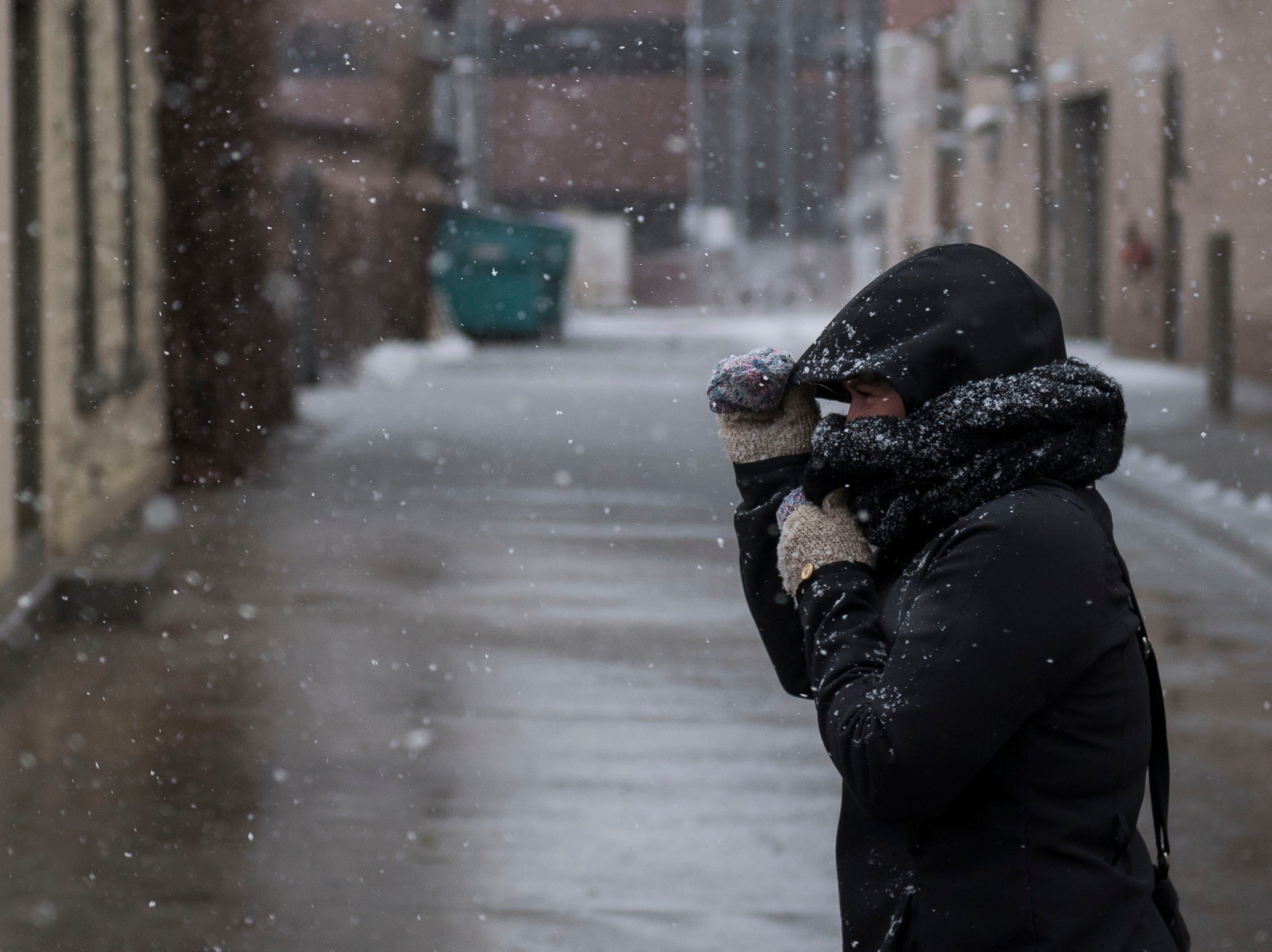 Hair stylist Jacque Buyck shields her face from the blowing snow as she head to work in Old Town on Wednesday morning, March 13, 2019, in Fort Collins, Colo.