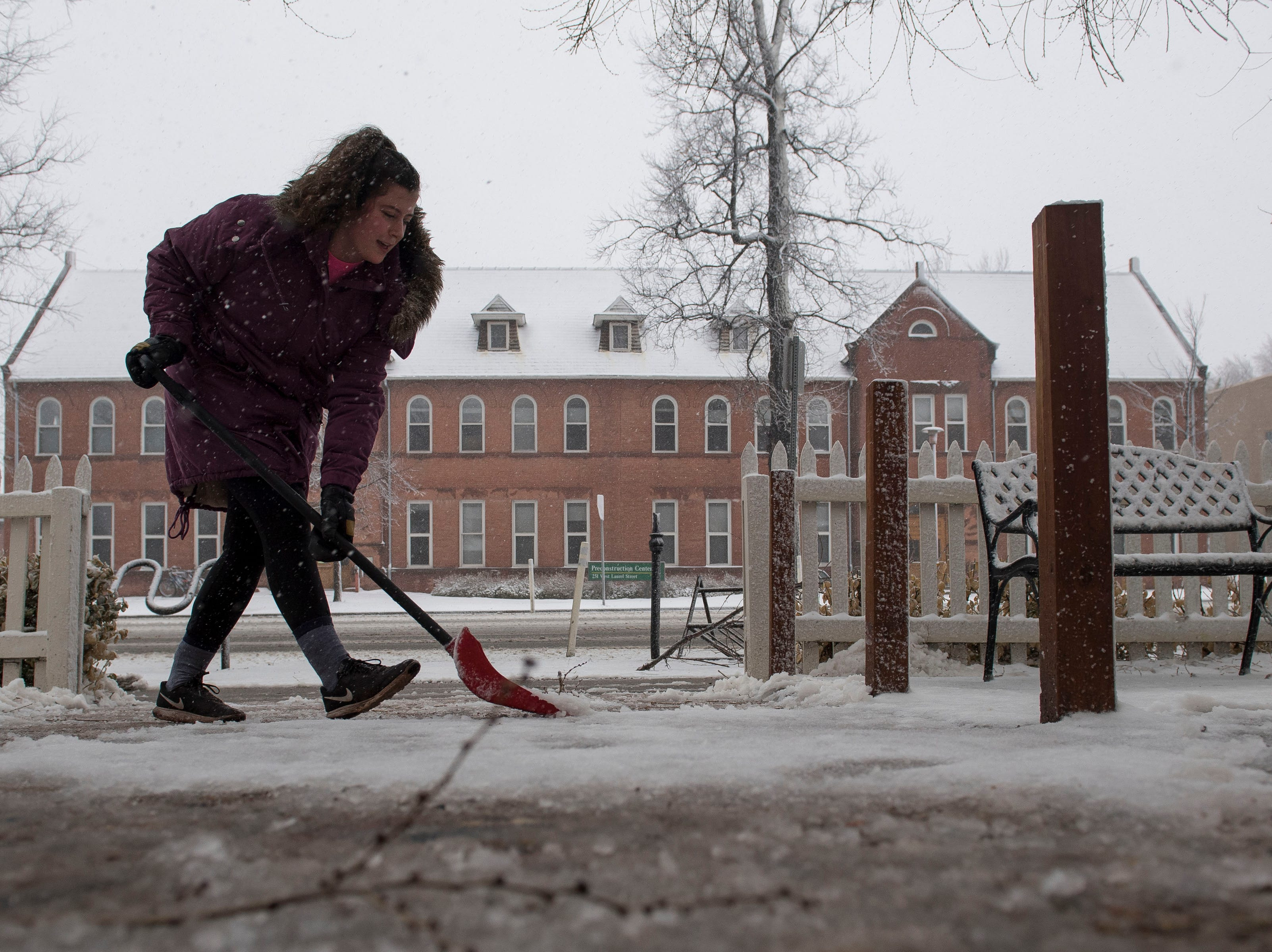 Hostess at The Rainbow, Vivian Stuart, shovels the front entrance of the restaurant during a snowstorm on Wednesday, March 13, 2019, in Fort Collins, Colo.