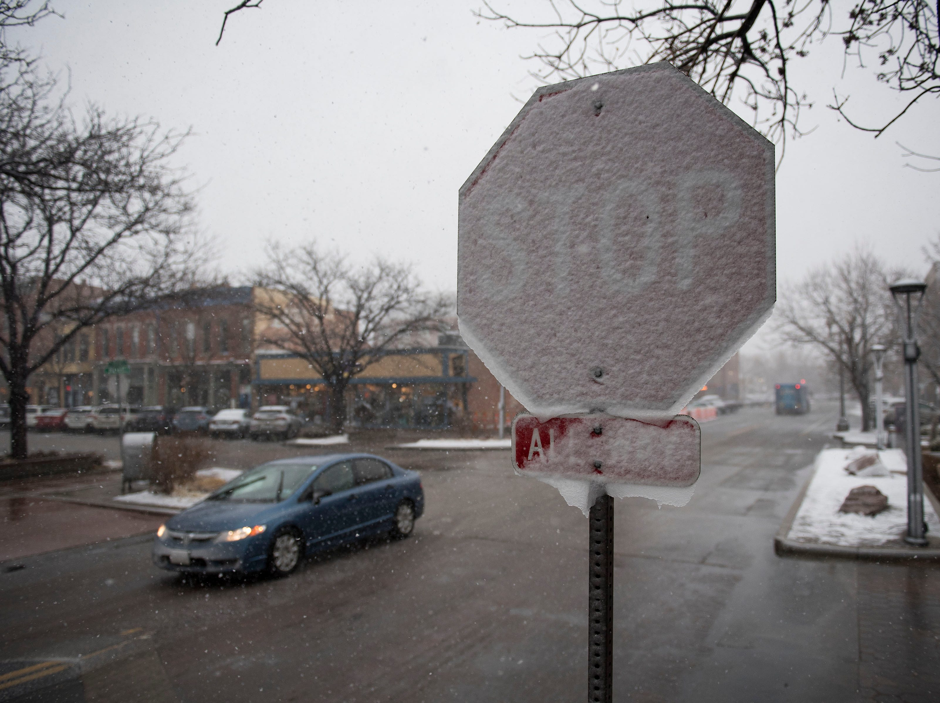 Snow sticks to a West-facing stop sign in Old Town on Wednesday, March 13, 2019, in Fort Collins, Colo.