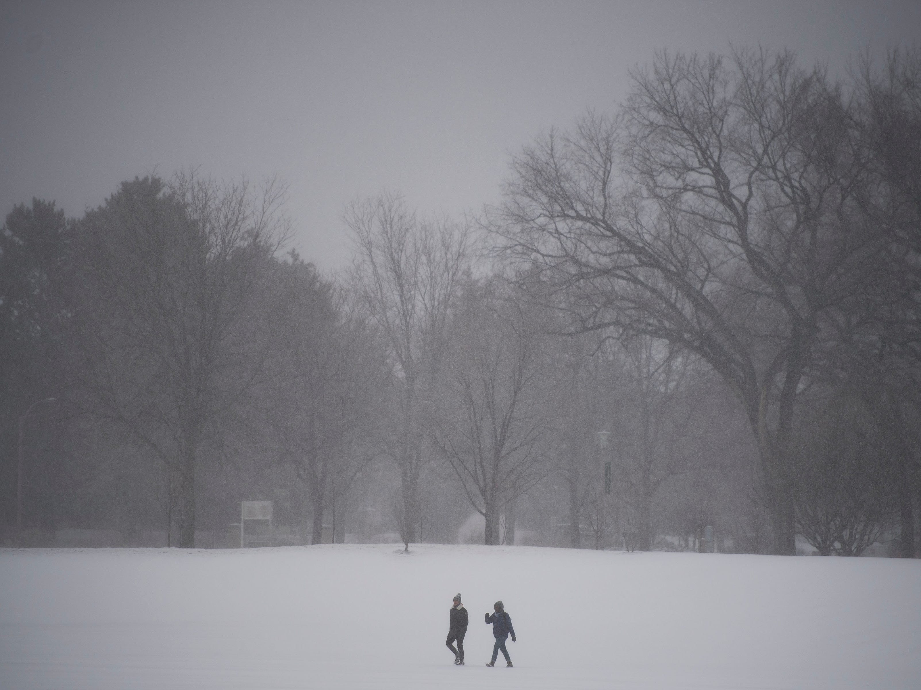 People walk through a snowy field just West of the Lory Student Center on Colorado State University's campus on Wednesday, March 13, 2019, in Fort Collins, Colo.