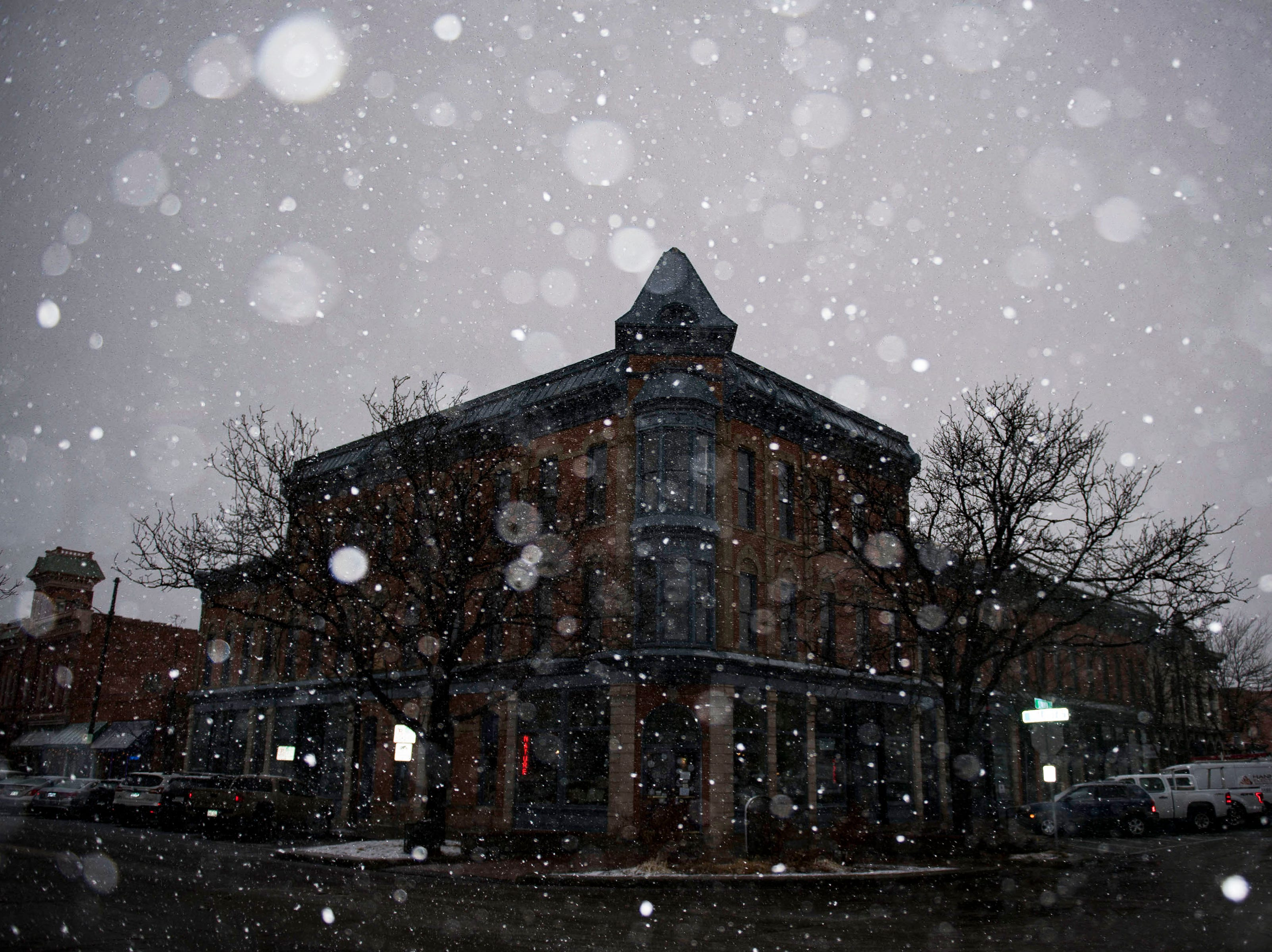 Snow falls in Old Town Square on Wednesday, March 13, 2019, in Fort Collins, Colo.