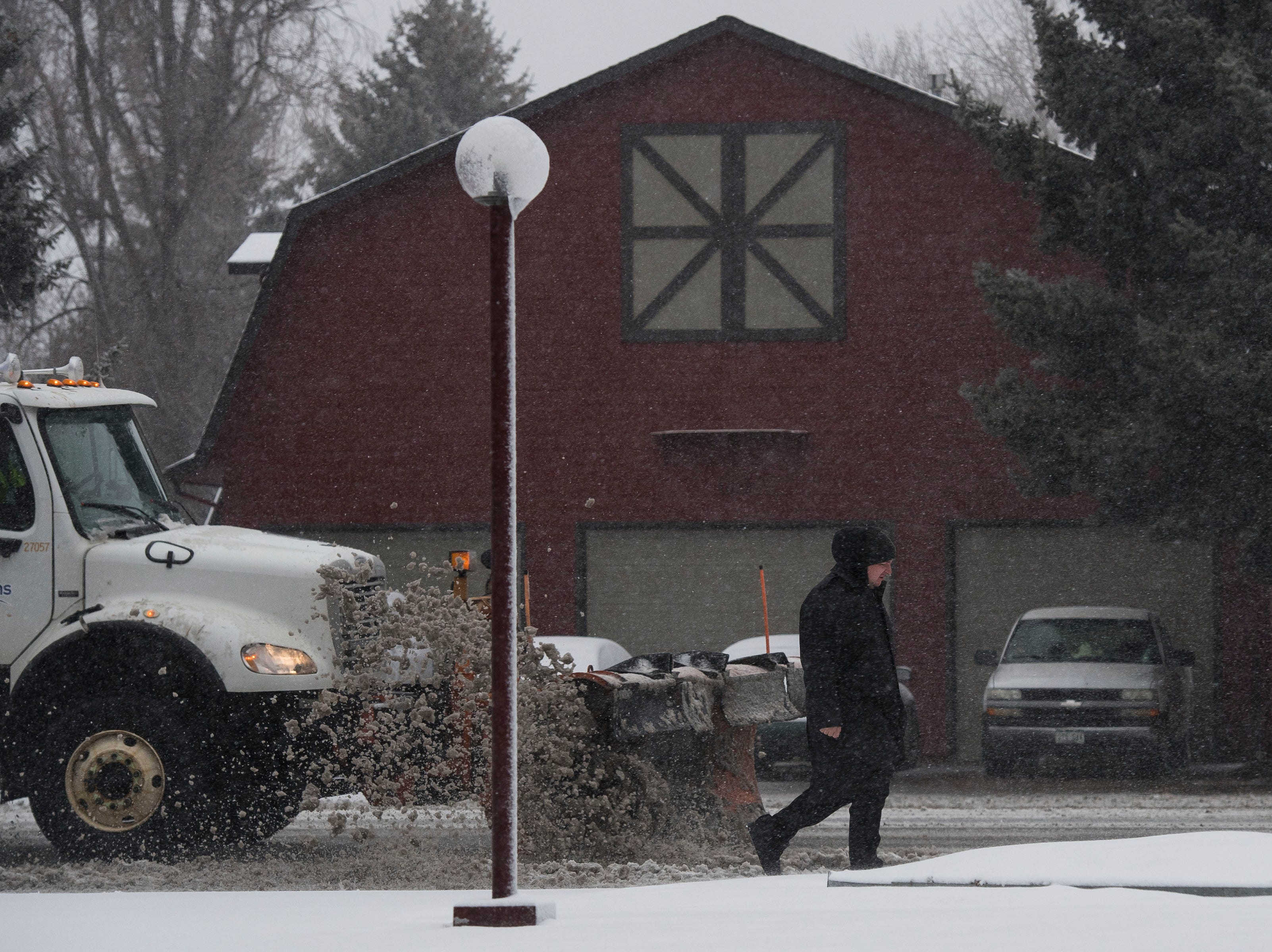 A snow plow clears the outside lane of South Lemay Avenue on Wednesday, March 13, 2019, in Fort Collins, Colo.