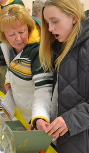 Hayden Beekman, right, appears surprised as she and her grandmother Nancy Gering look over the 1910 Oconto HIgh School yearbook, one of several old volumes on display courtesy of Farnsworth Public Library at the City of Oconto Sesquicentennial Celebration Kickoff Reception on March 11.