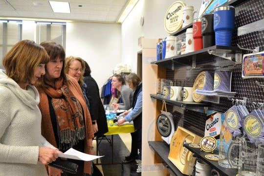 Diane LeBreck and Wendy Spice look over a display of Oconto Sesquicentennial and Oconto merchandise offered by Jeff Larmay of Vital Signs at the Sesquicentennial Celebration Kickoff Reception on March 11 at the Oconto Municipal Building.