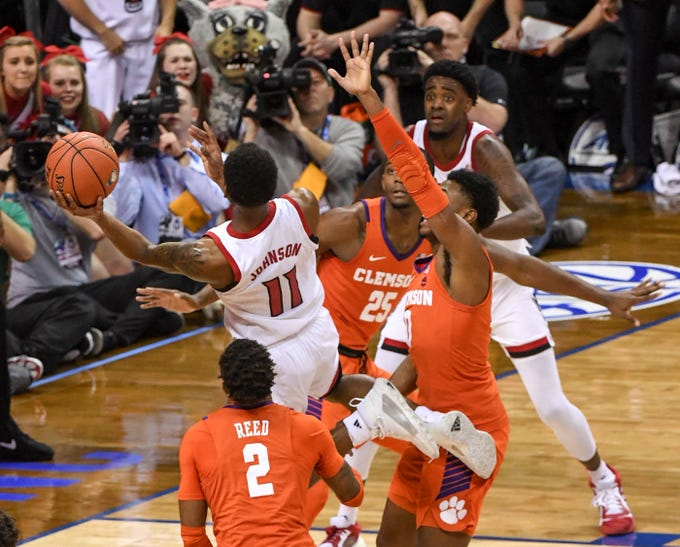 N.C. State guard Markell Johnson(11) is fouled by Clemson center Clyde Trapp (0), near Marcquise Reed (2), and Aamir Simms (25) during the second half at the Spectrum Center in Charlotte, N.C. Tuesday, March 12, 2019. Johnson made both free throws to give N.C. State a 59-58 lead.