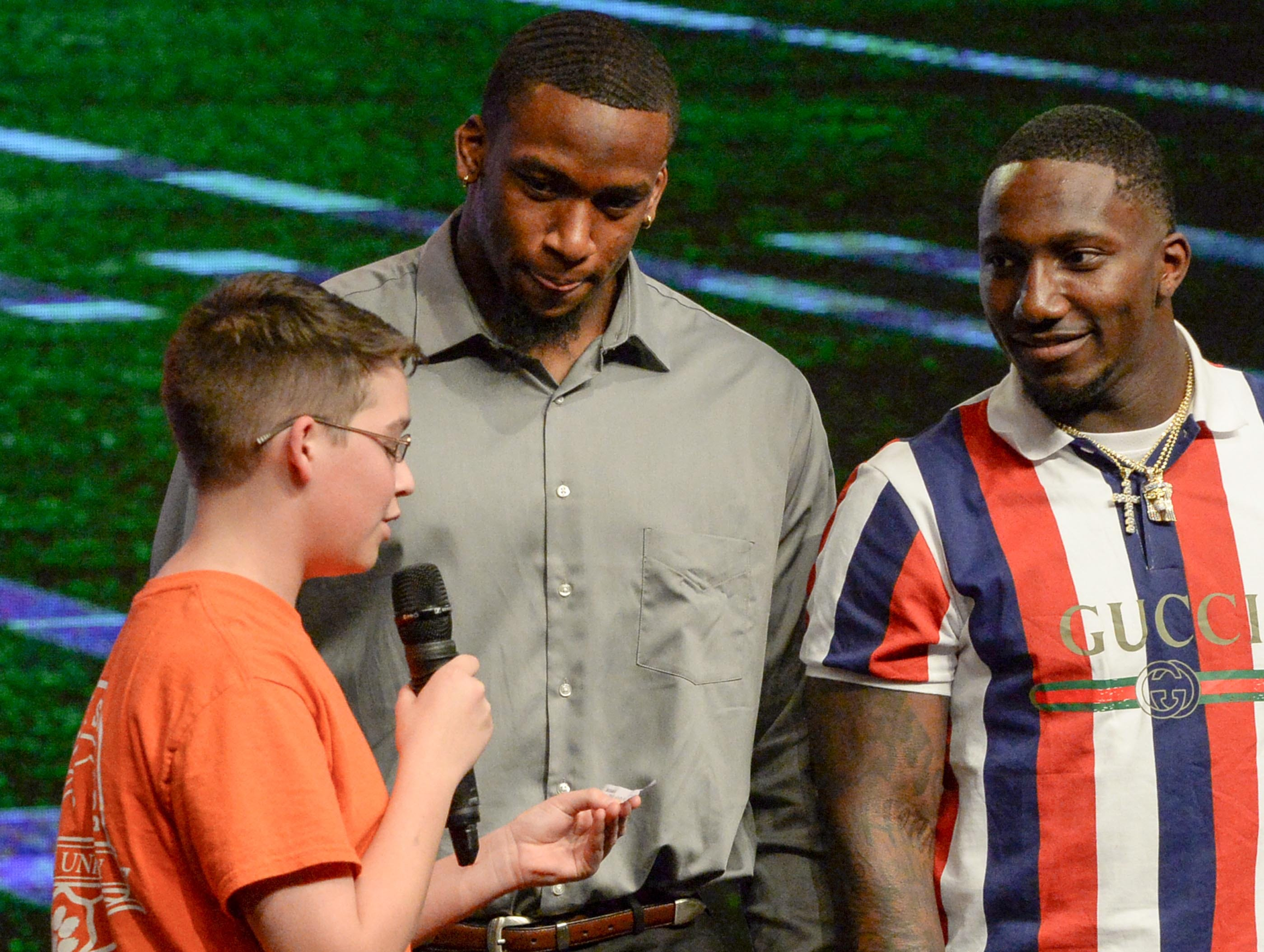 Former Clemson Tiger Clelin Ferrell, left, and Deebo Samuel, right, South Carolina Gamecock football player, listen to Franklin Ruby, an eighth grade student from Riverside Middle School in Pendleton ask a question about their most influential person in their lives during the Coaches 4 Character event at Relentless Church in Greenville Tuesday.