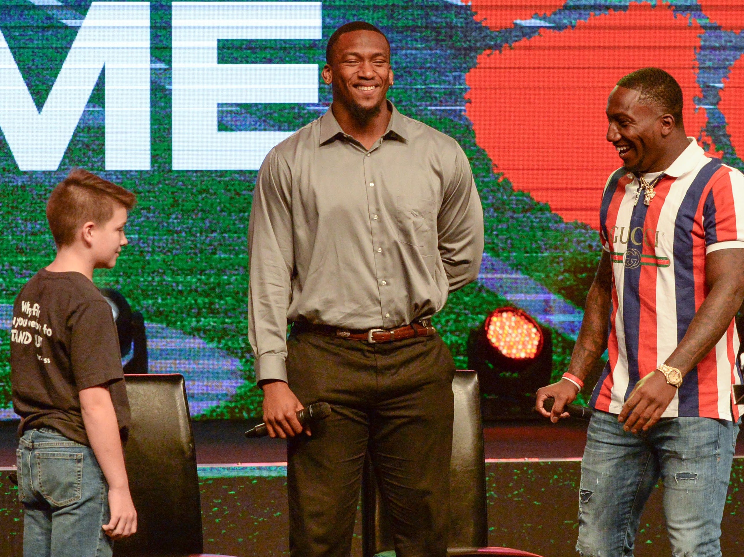 """Former Clemson Tiger Clelin Ferrell, left, and Deebo Samuel, right, South Carolina Gamecock football player, listen to Dax Allen of La France Elementary ask a question about what they would do with a large amount of money from professional football, during the Coaches 4 Character event at Relentless Church in Greenville Tuesday. """"Put it in the bank,"""" both said."""