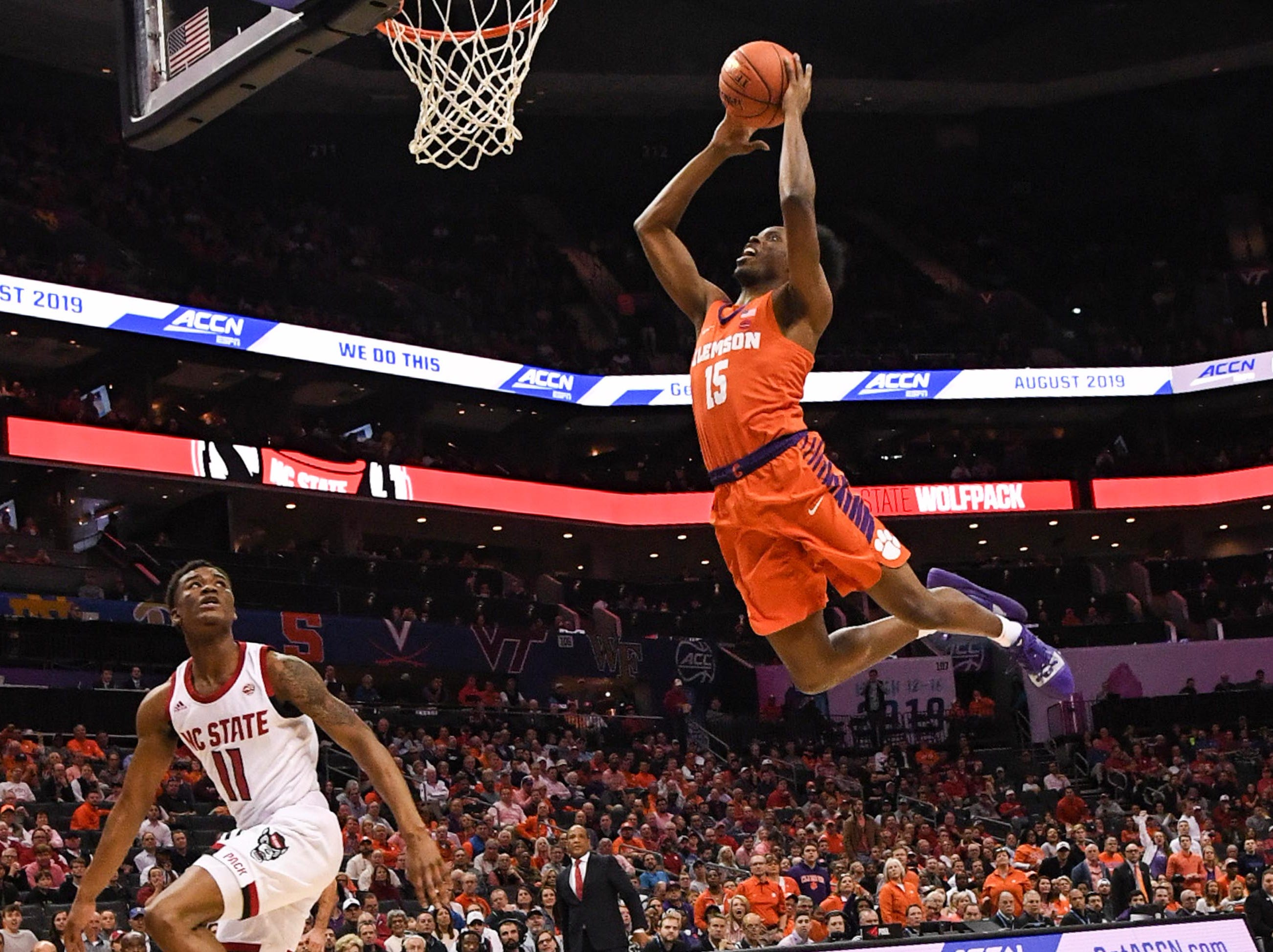Clemson forward John Newman (15) dunks near N.C. State guard Markell Johnson(11) during the first half at the Spectrum Center in Charlotte, N.C. Tuesday, March 12, 2019.