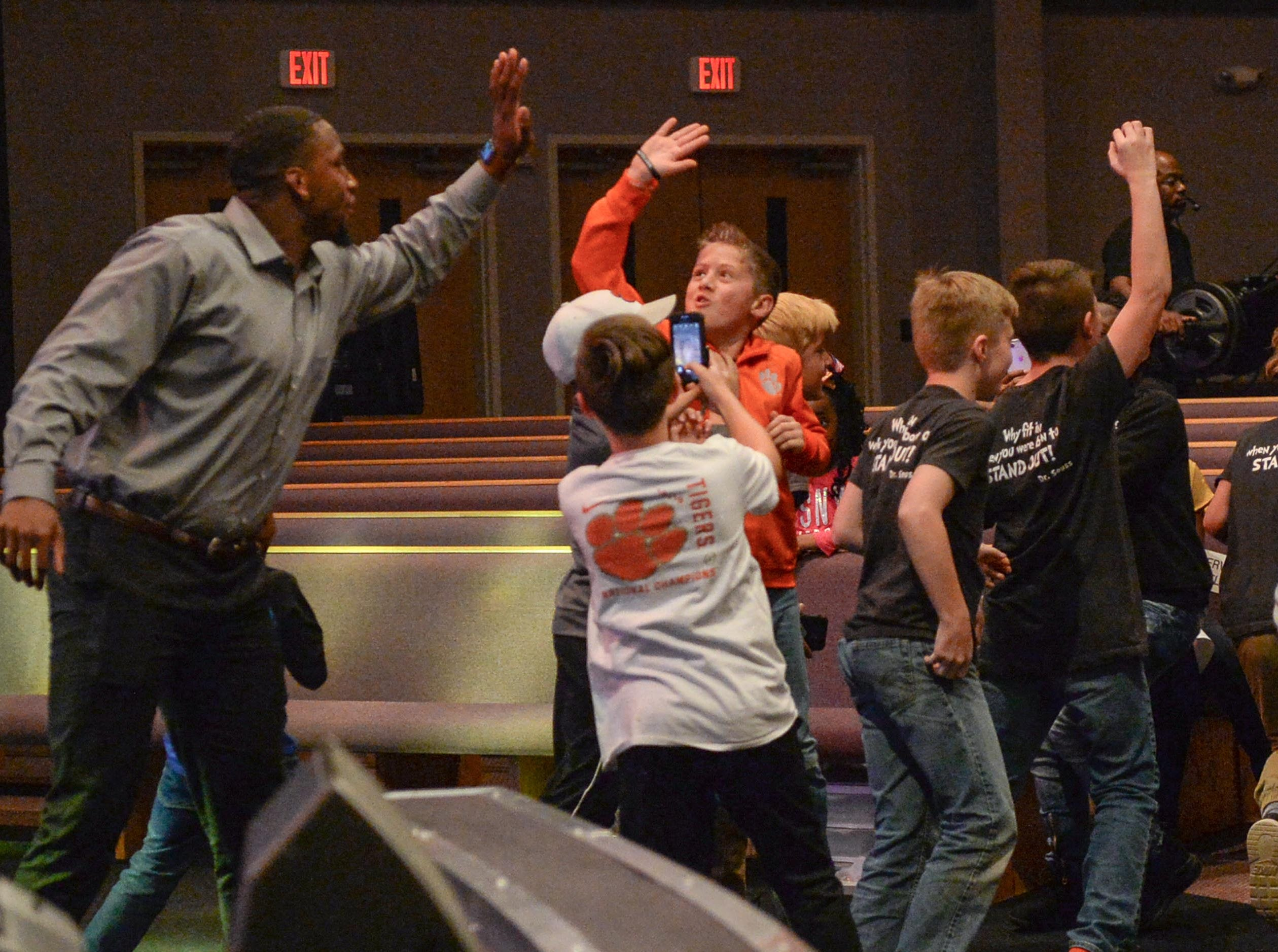 Former Clemson Tiger Clelin Ferrell, left, gives a high five to students attending the Coaches 4 Character event at Relentless Church in Greenville Tuesday.